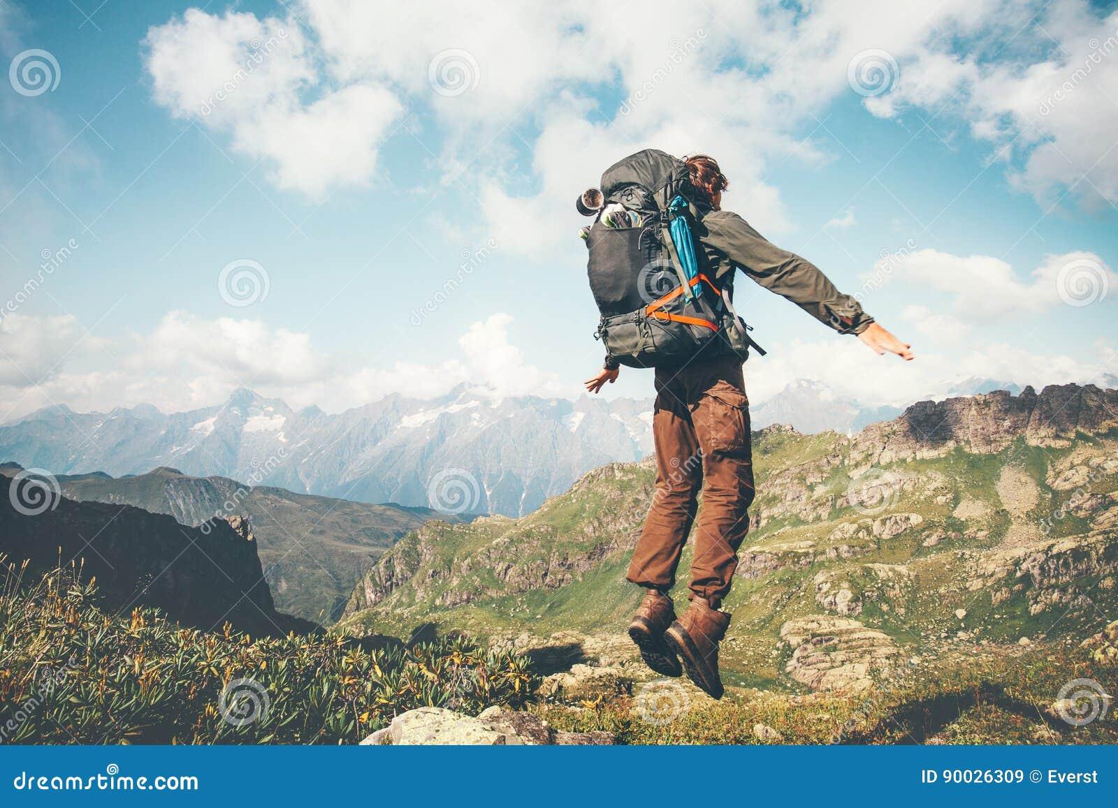 Springende Levitation des glücklichen Mannes mit schwerem Rucksack