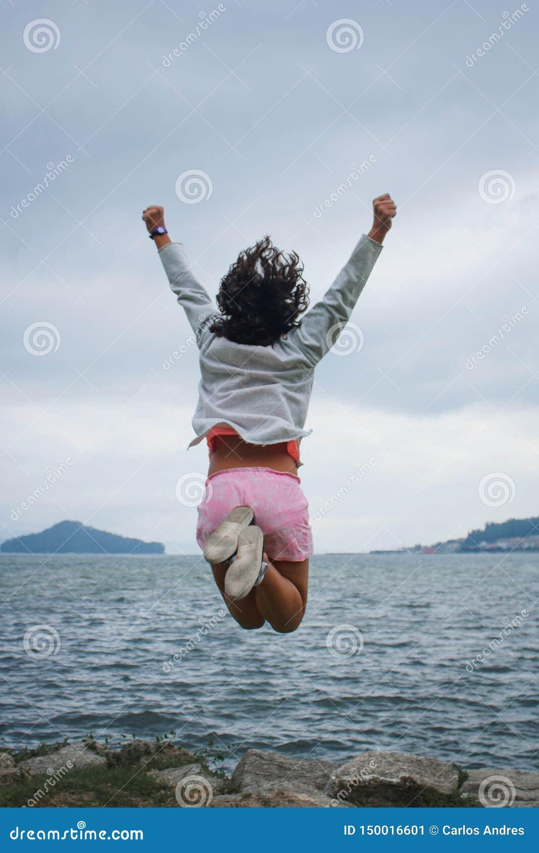 Springendes Hoch des jungen Mädchens, welches das Meer gegenüberstellt