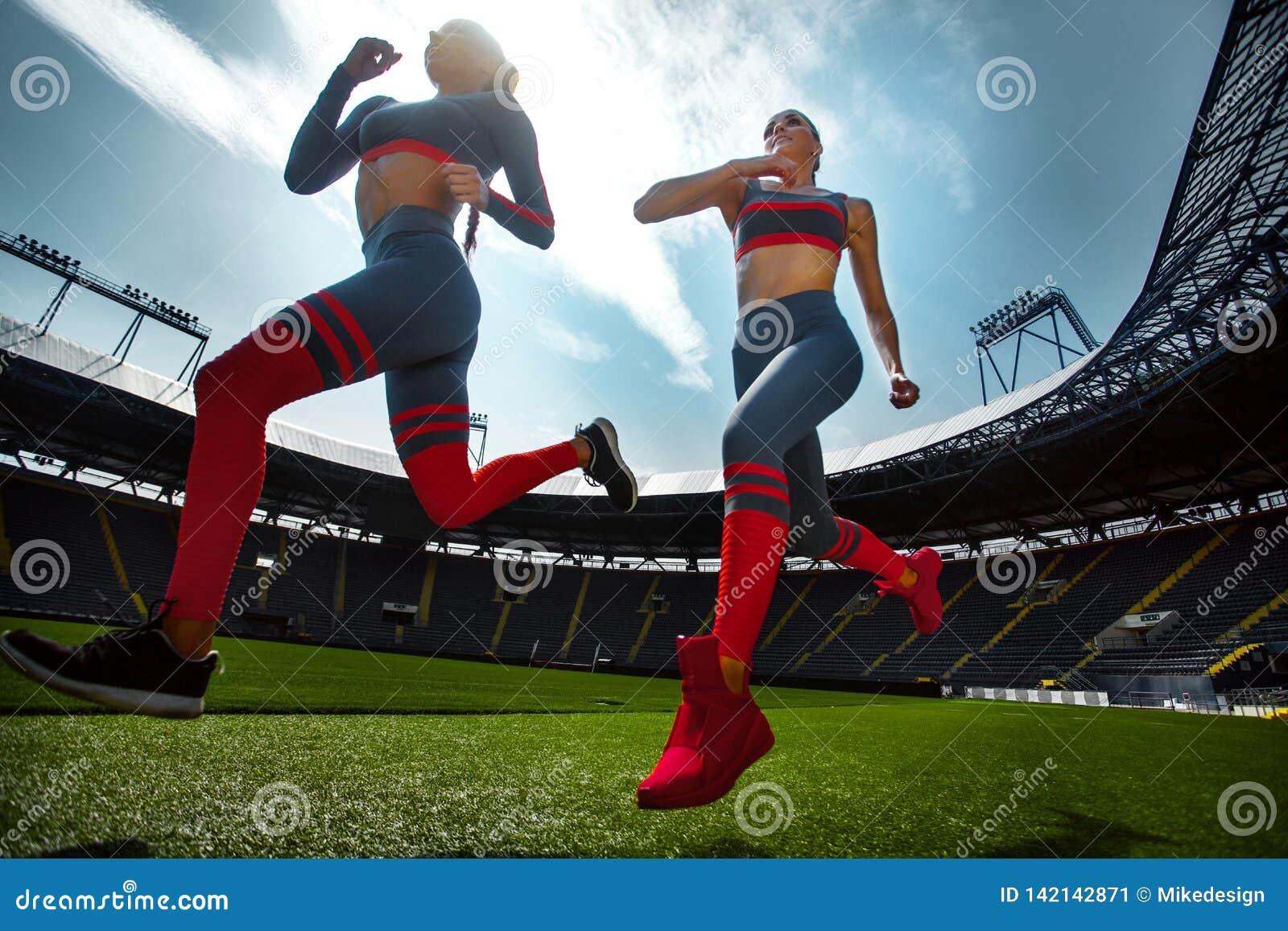 Sprinter sportif fort de femme, courant sur le stade portant dans les vêtements de sport Motivation de forme physique et de sport