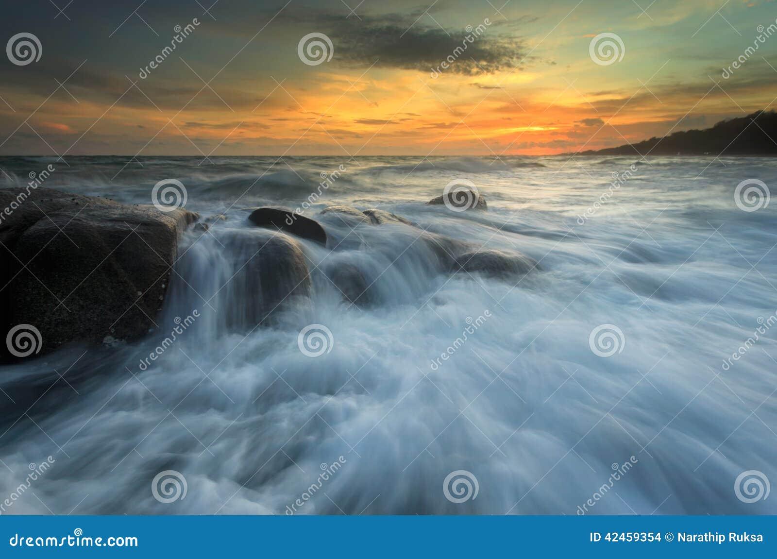 Spritzen der Welle mit schönem Sonnenuntergang