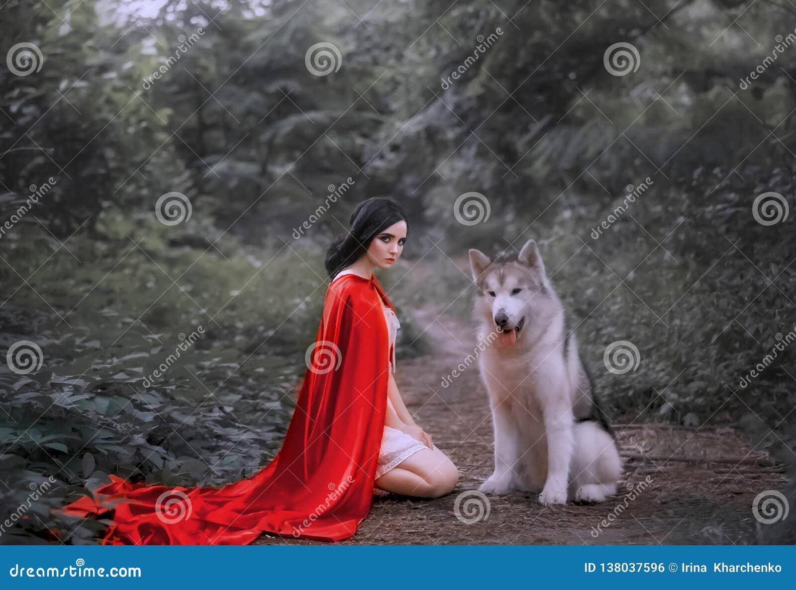 Sprookje over rood GLB, donker-haired meisje op grond in dik bos in korte witte lichte kleding, lange scharlaken mantel