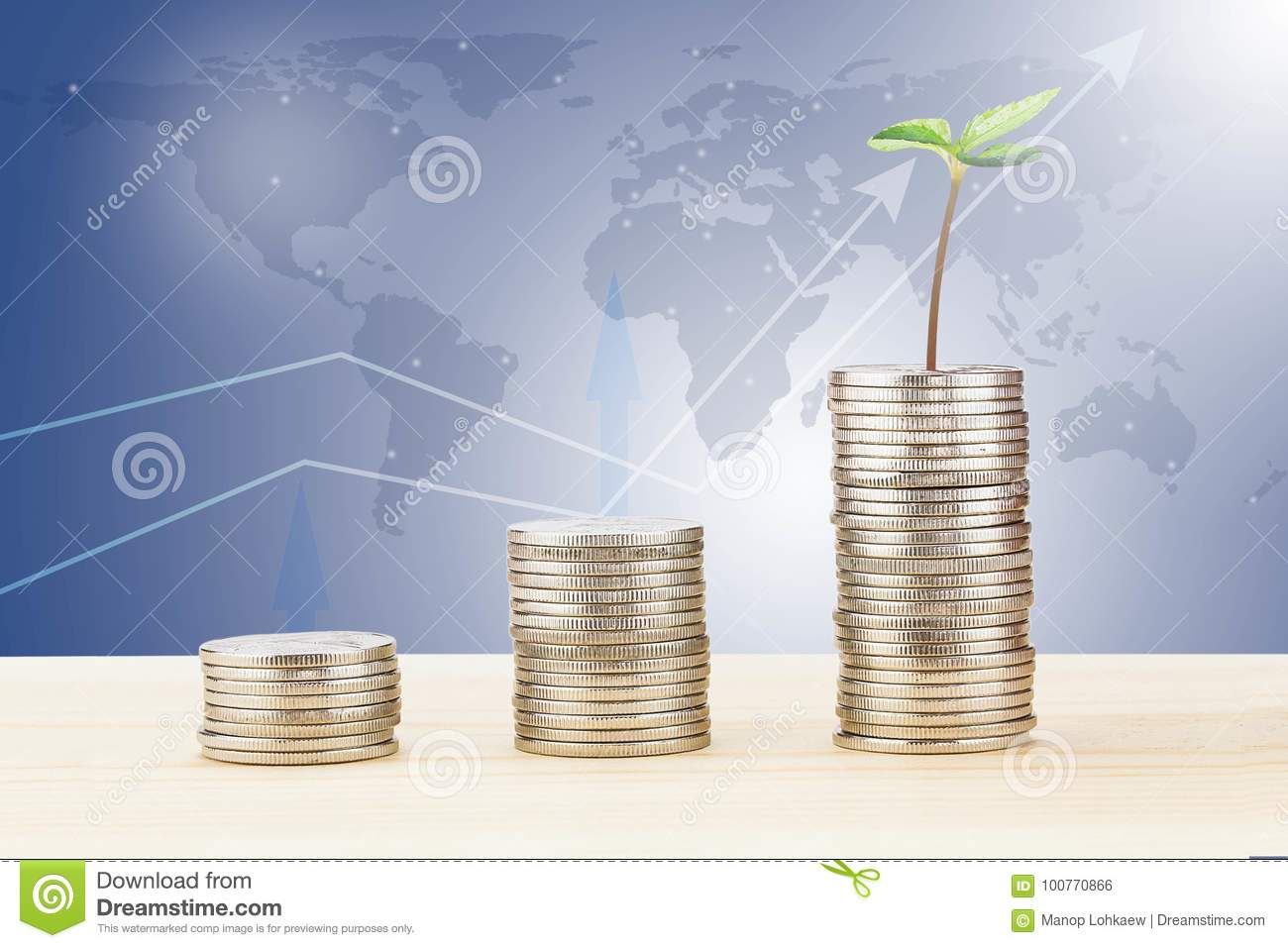 Sprout growing from stack of coins on wooden desk on blurred world map and line graph background