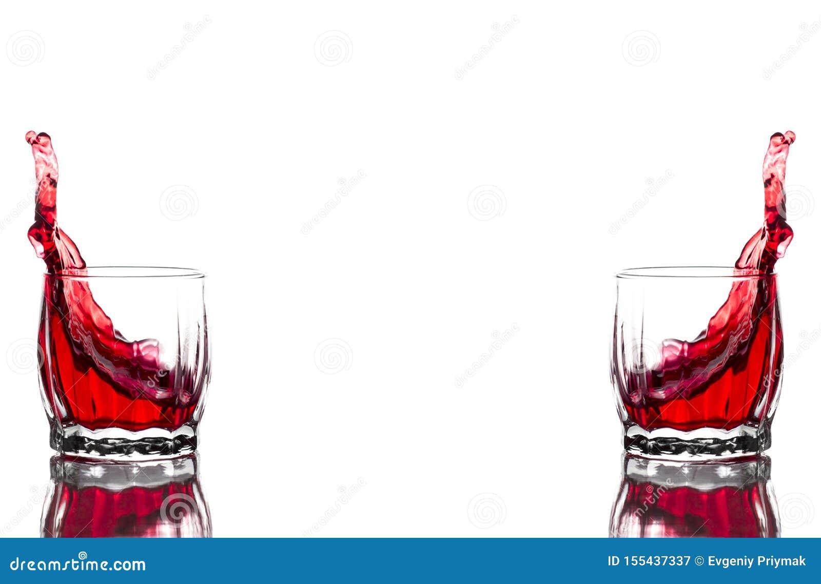 Spruzzata di succo rosso, vino in un vetro costolato di vetro del whiskey su un fondo bianco