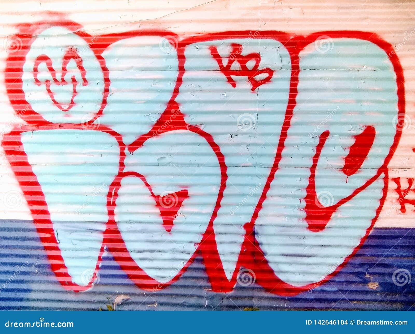 Spruzzo variopinto dei graffiti dipinto su una parete del metallo