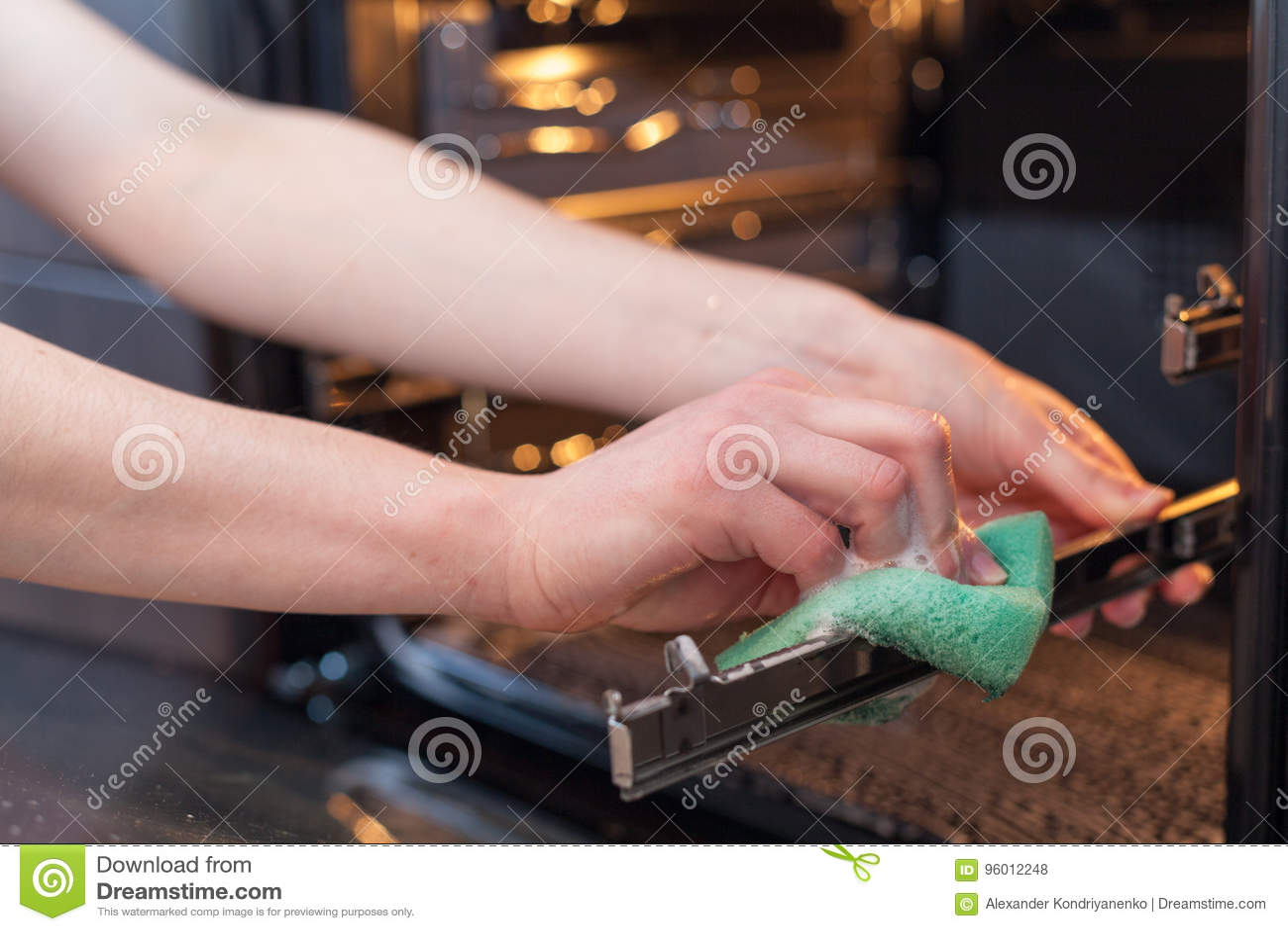 Sprzątania i housekeeping pojęcie Szorować piekarnika i kuchenkę Zakończenie up żeńska ręka z zieloną gąbką czyści kuchnię