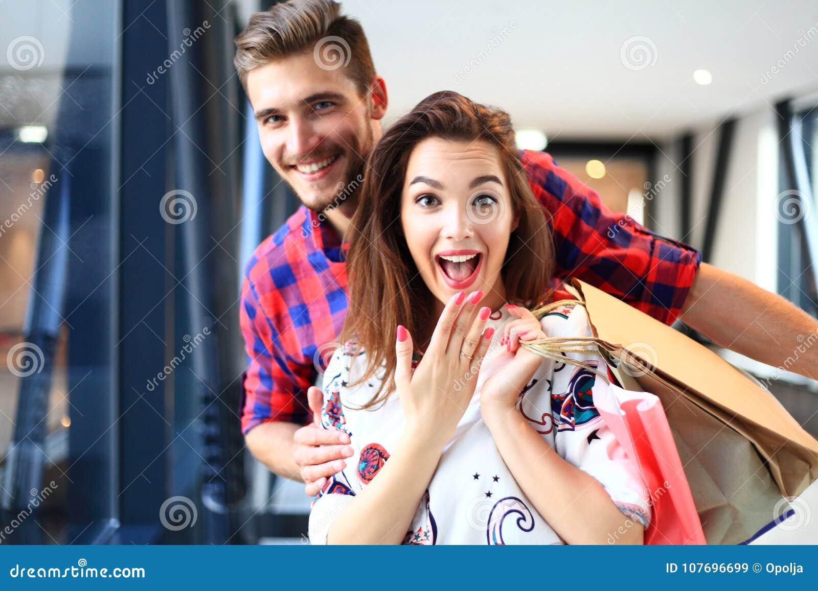 Sprzedaż, konsumeryzm i ludzie pojęć, - szczęśliwi potomstwa dobierają się z torba na zakupy chodzi w centrum handlowym