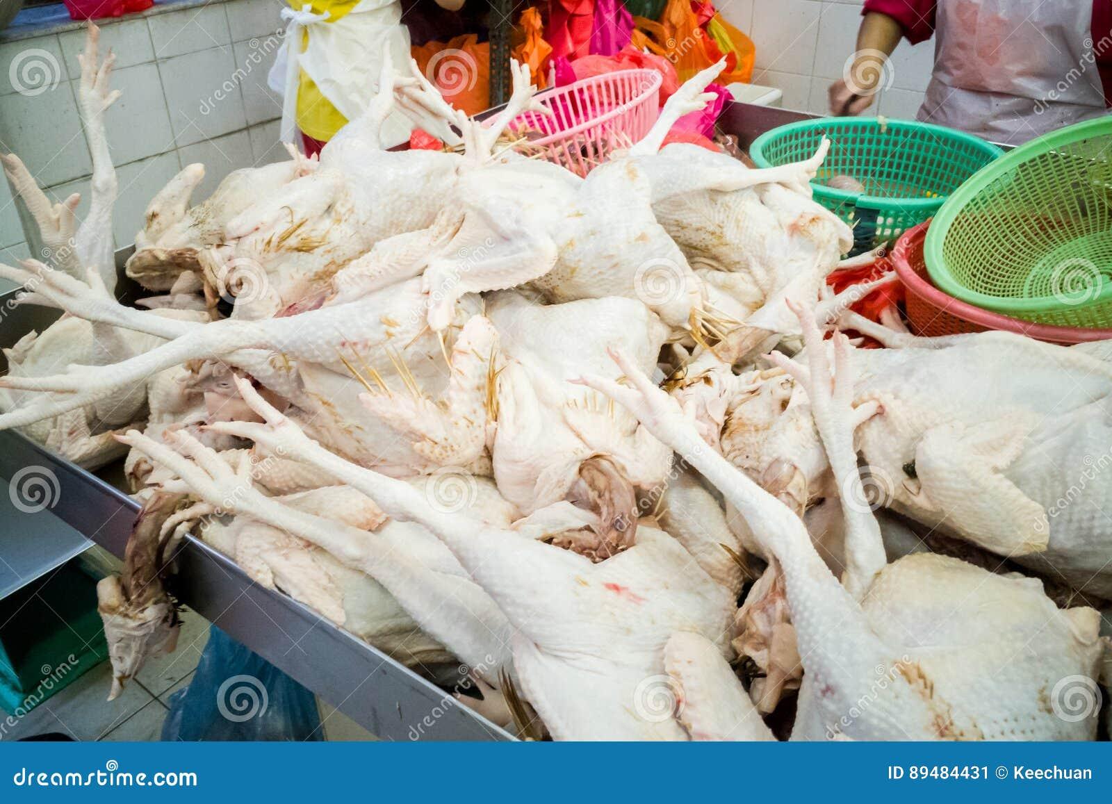 Sprzedawca sprzedaje świeżo ubitego całego kurczaka w rynku kramu