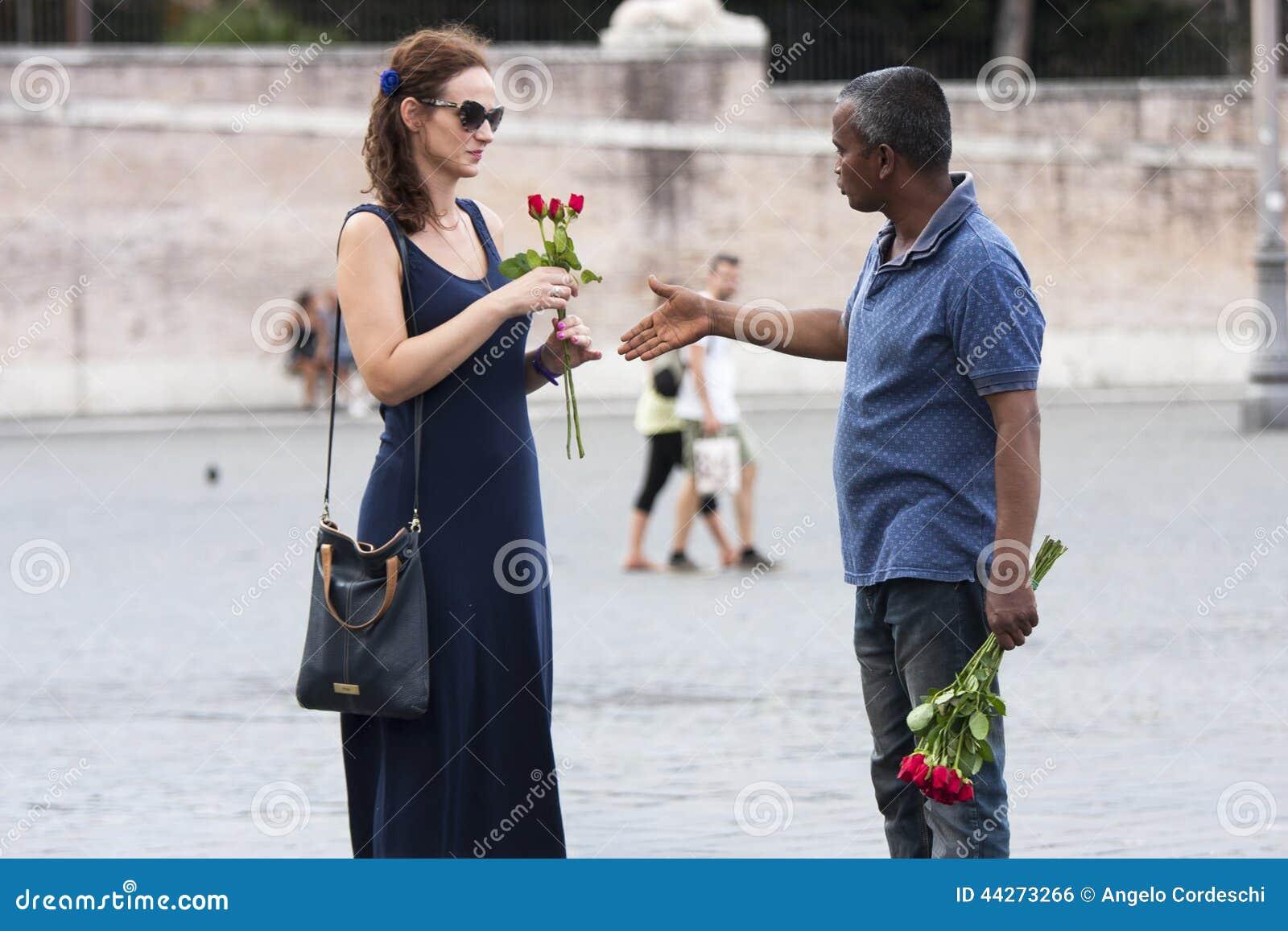 Sprzedawca uliczny róże z turystą