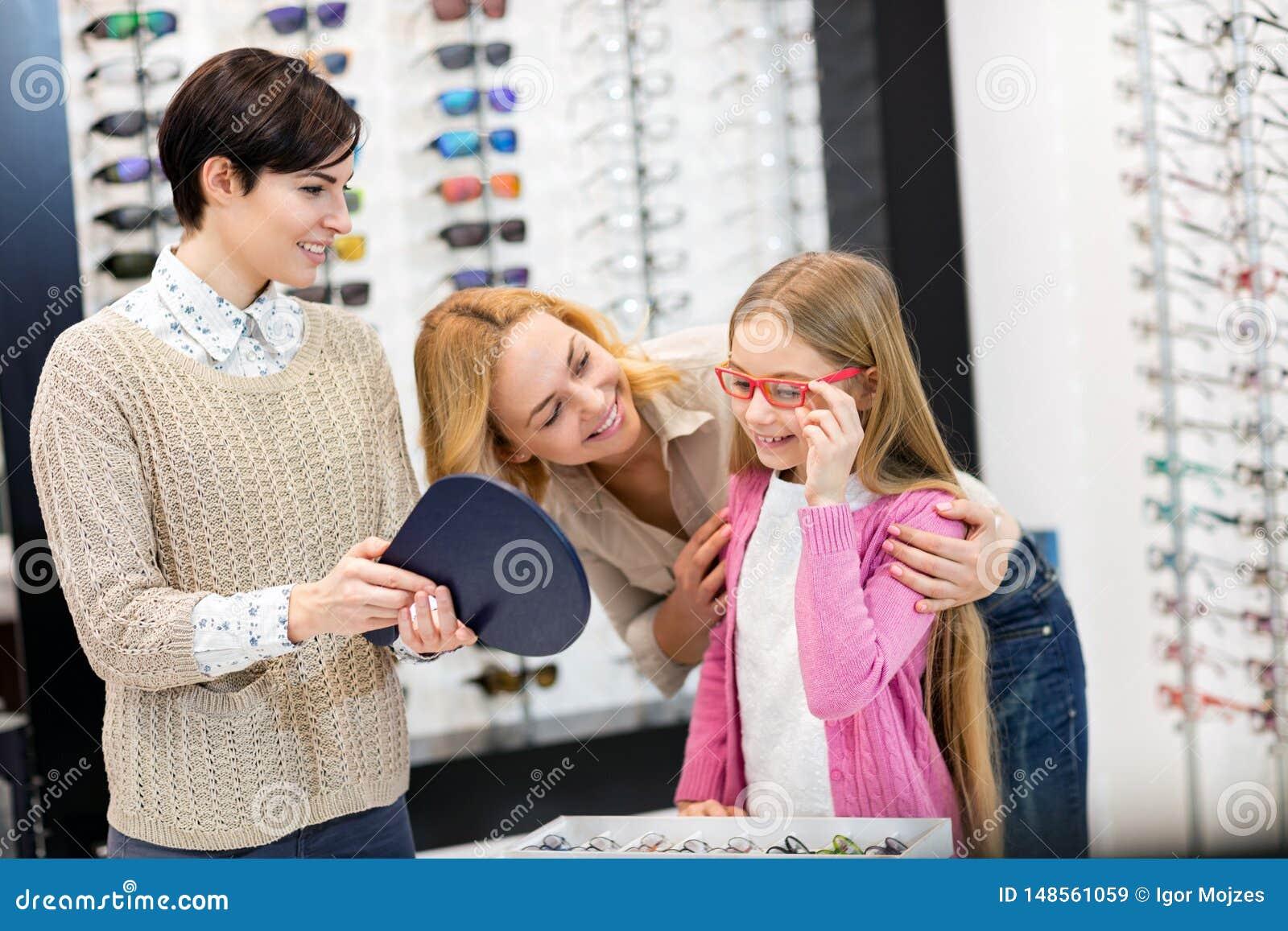 Sprzedawczyni chwyta lustro podczas gdy dziecko pr?by ramy dla eyeglasses