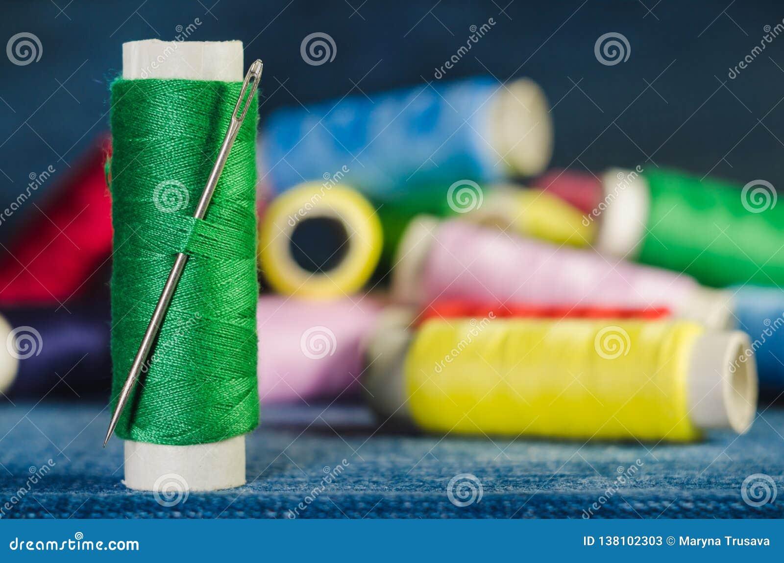 Spule des grünen Fadens mit einer Nadel auf dem Hintergrund von Spulen von farbigen Faden auf einem Denim, Nahaufnahme