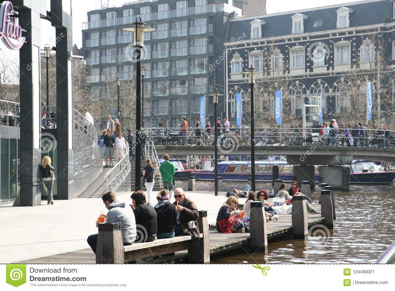 Square in the city. People relax near the water and in the cafe. A warm day in the city.