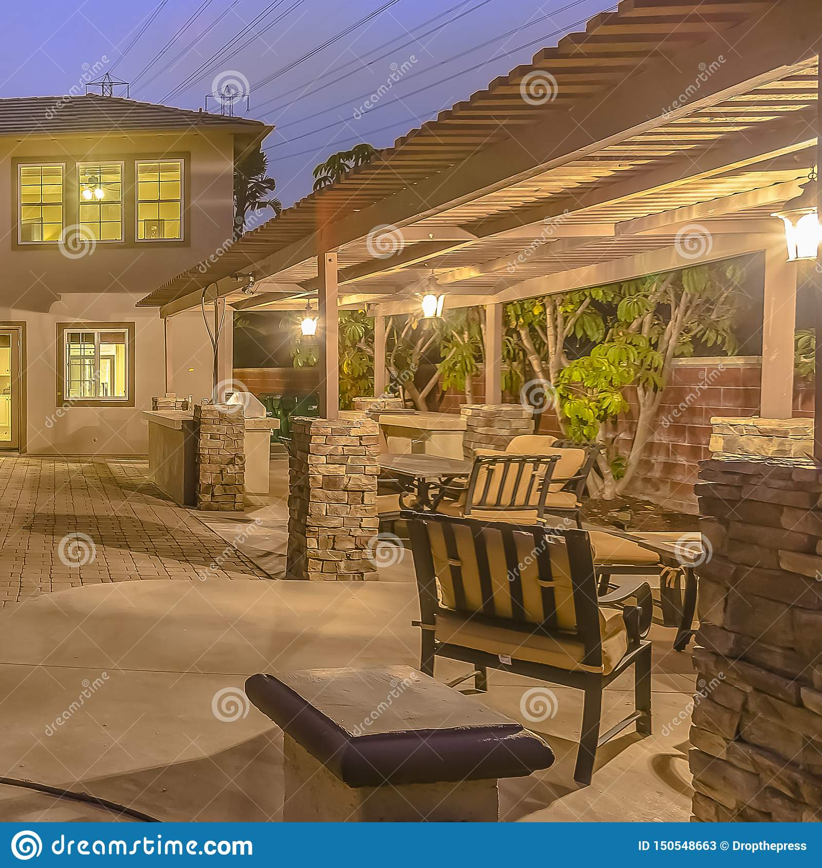 Square Frame Illuminated House With A Patio Accomodating An Outdoor Dining Area And Fire Pit Stock Image Image Of Table Square 150548663