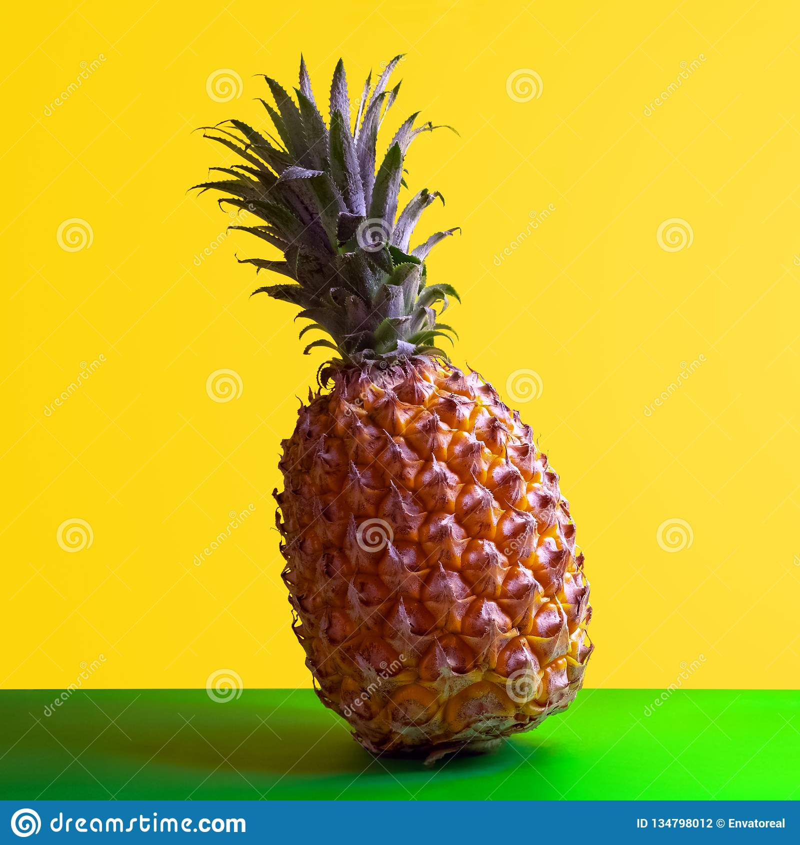 Square frame for pineapple advertising. Ripe sweet exotic fruit stands on a green table with a yellow background. Clipart for