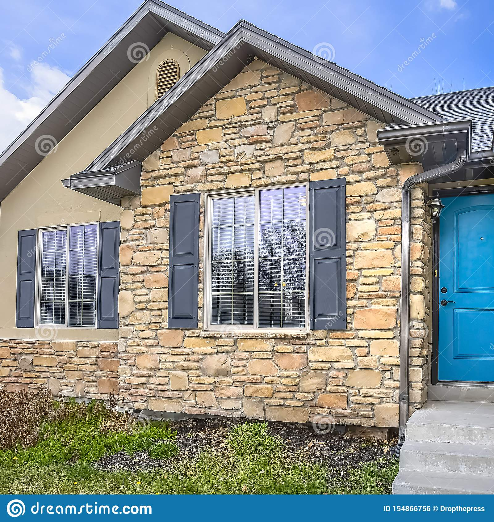 Square Home With Stairs Blue Front Door Stone Wall And