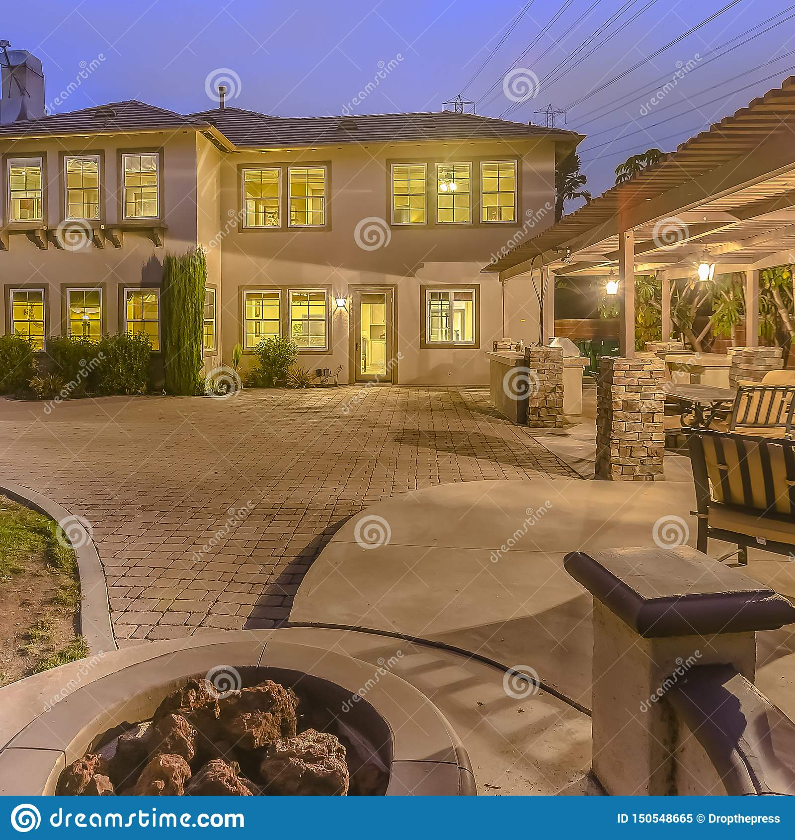Square Illuminated House With A Patio Accomodating An Outdoor Dining Area And Fire Pit Stock Image Image Of Bench Plants 150548665