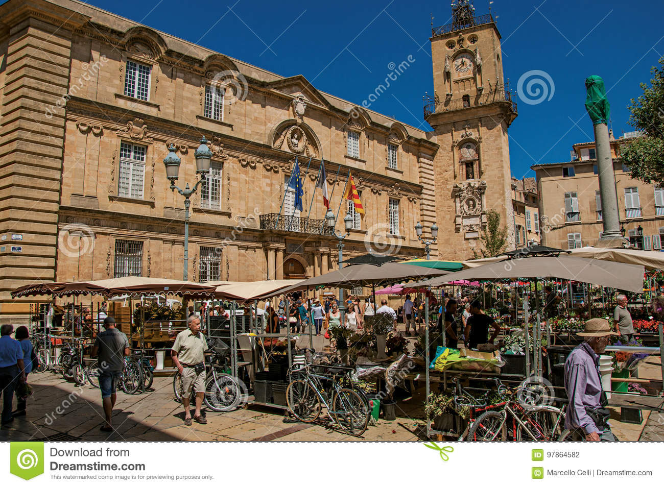 Square with market stall, people and clock tower in Aix-en-Provence,