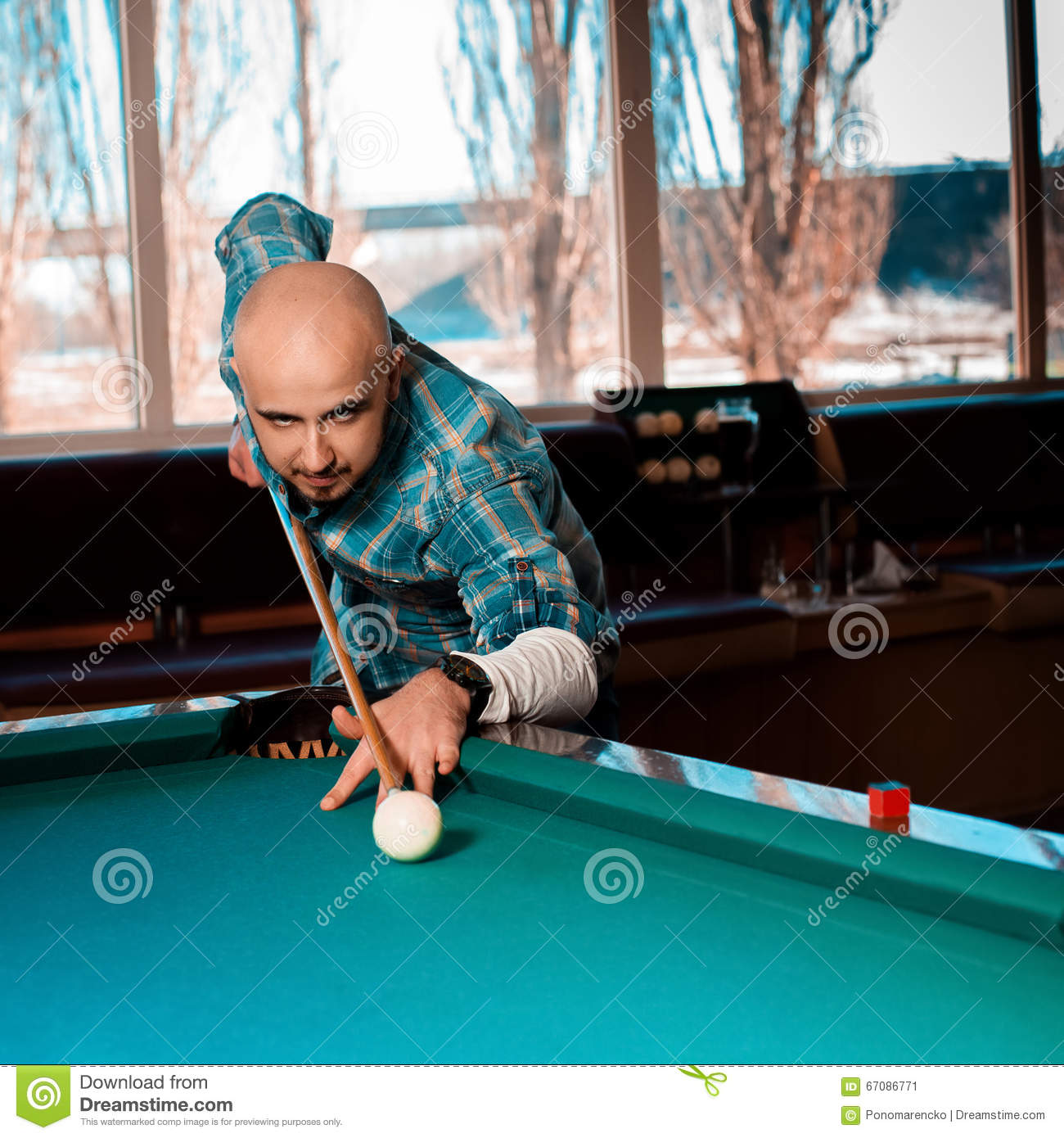 Square Photo Man preparing to hit the cue ball on a pool billiar