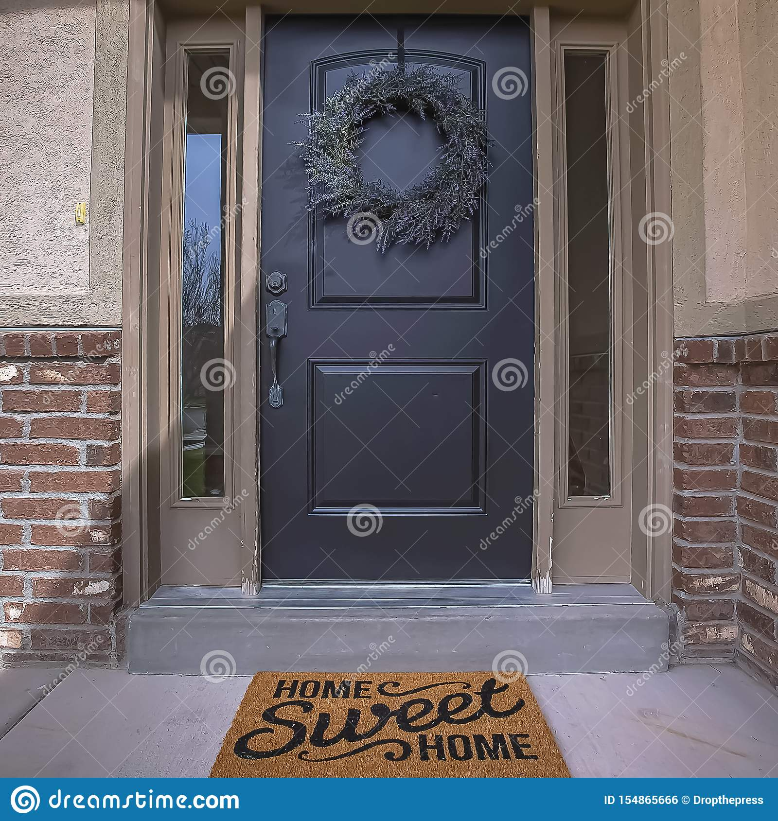 Square Wreath And Doormat On The Front Door With Sidelights