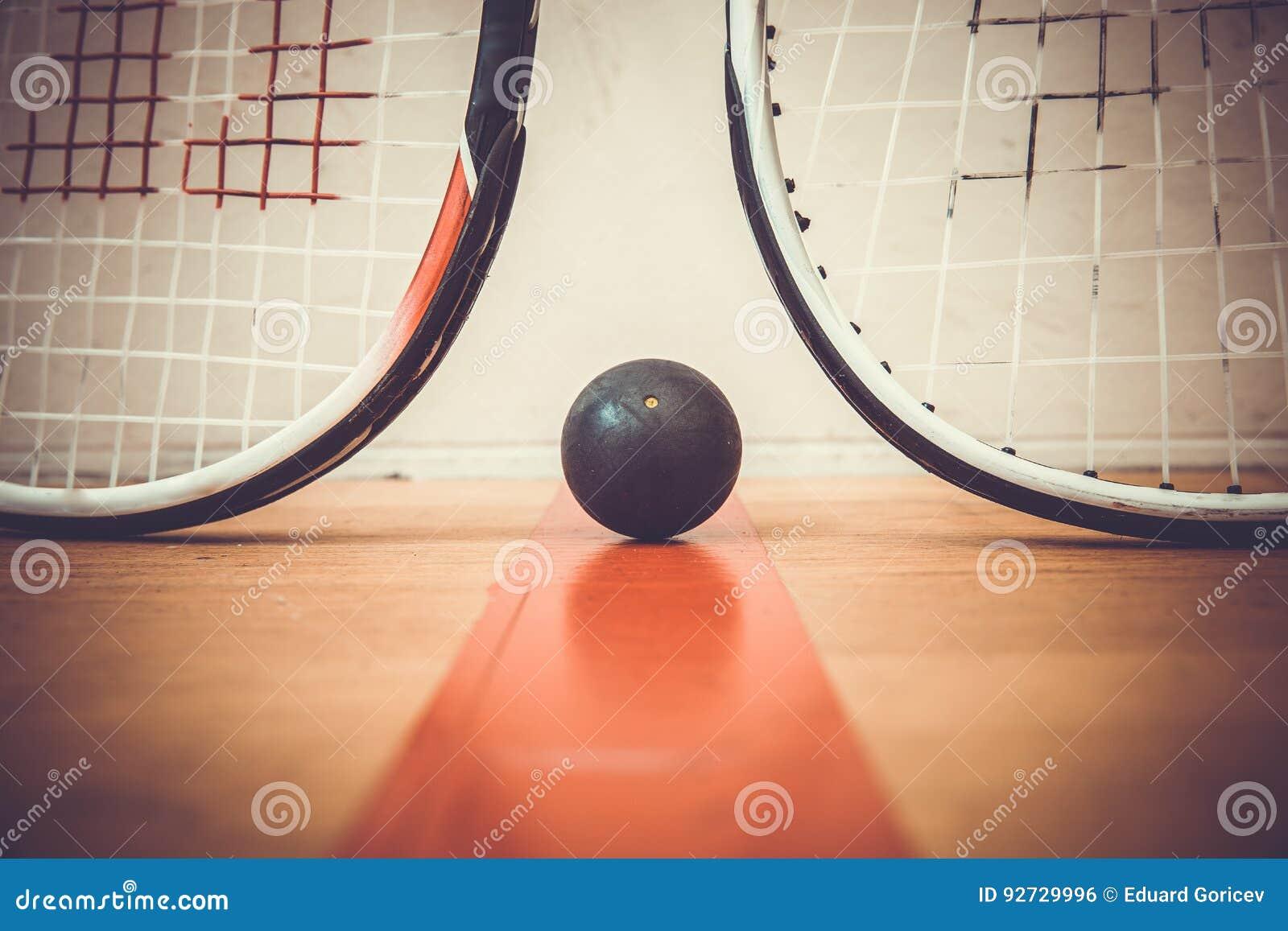 Squash ball between two squash rackets