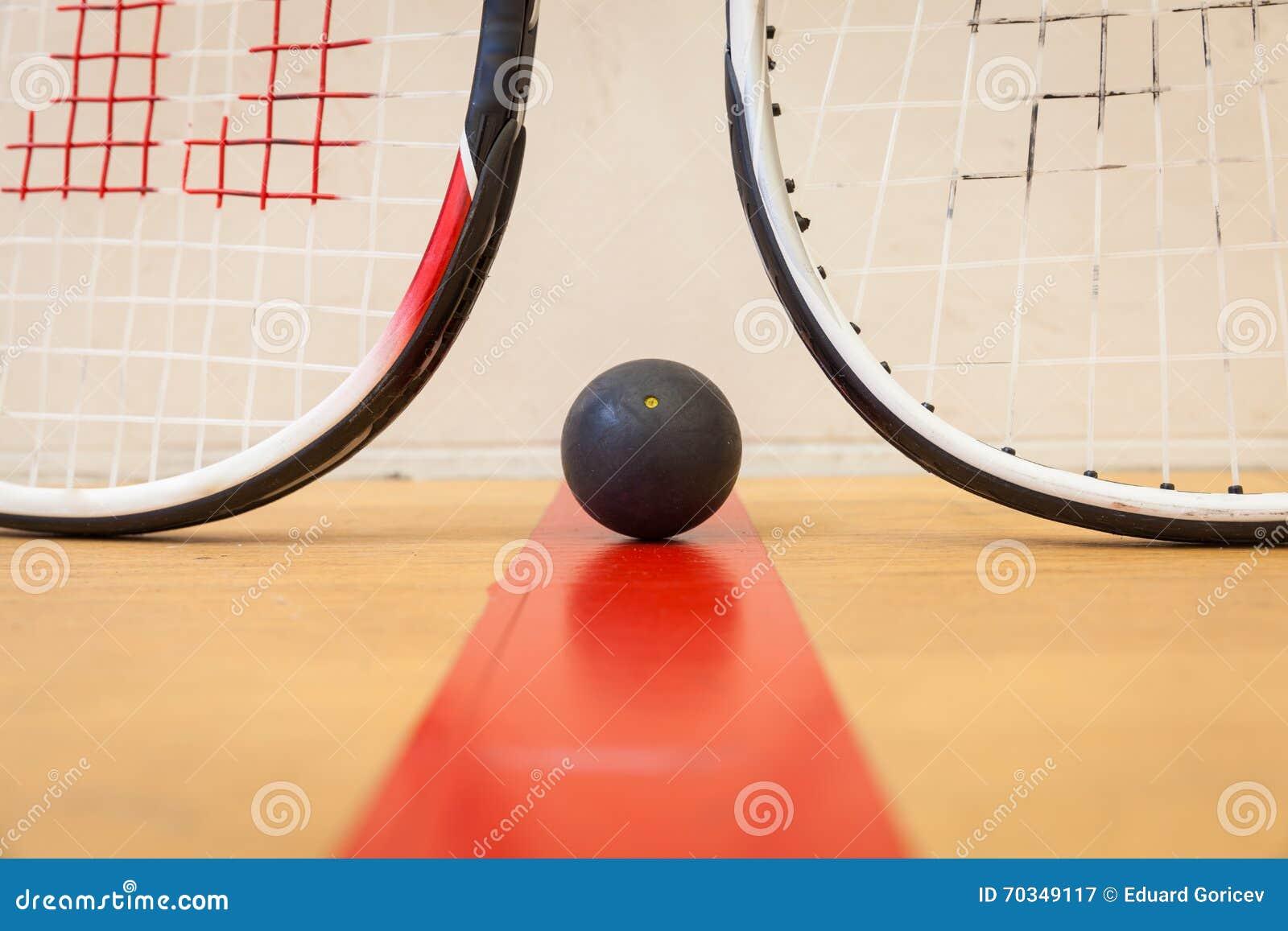 Squashboll mellan två squashracket