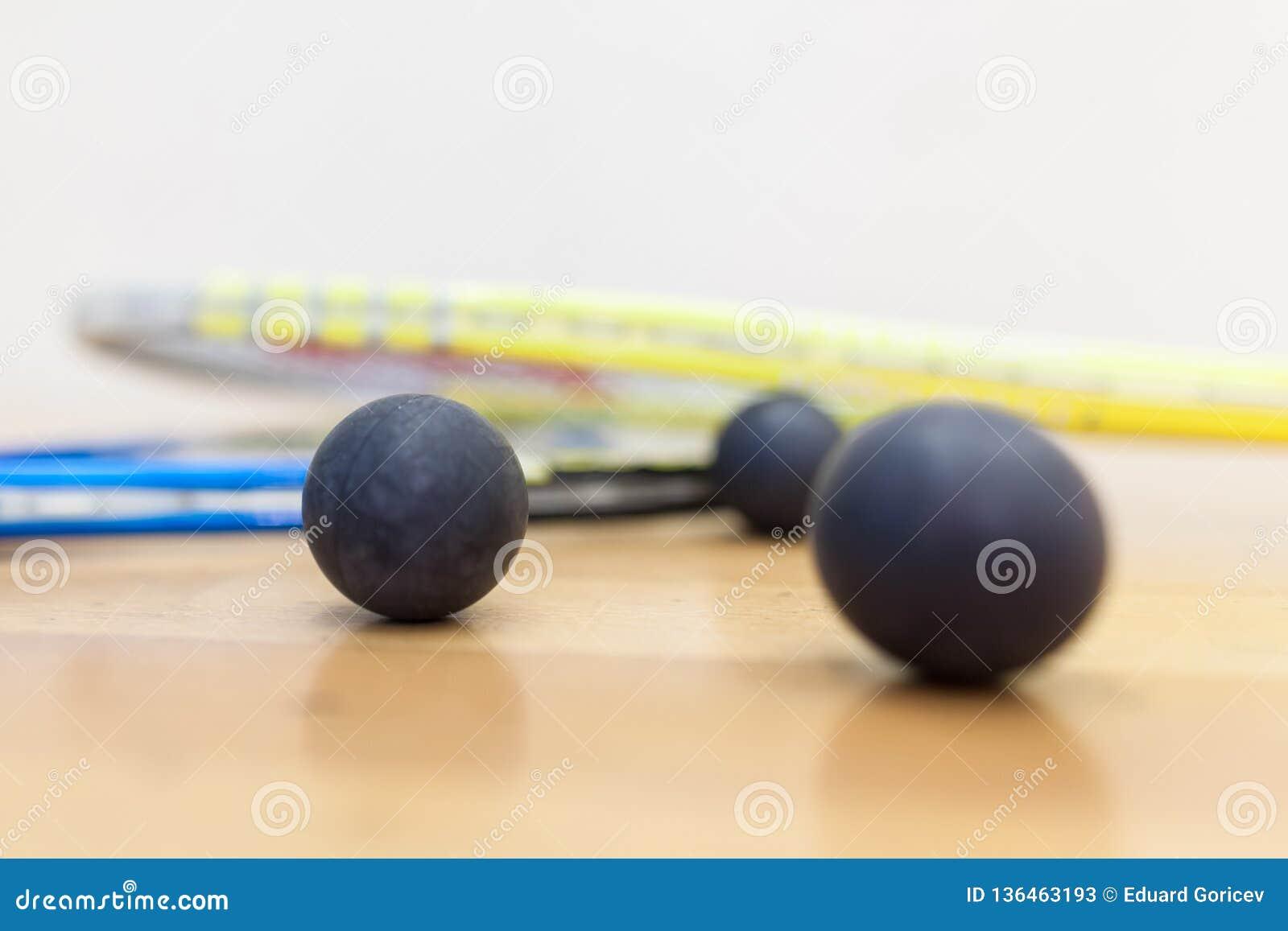 Squashracket och bollar på domstolen