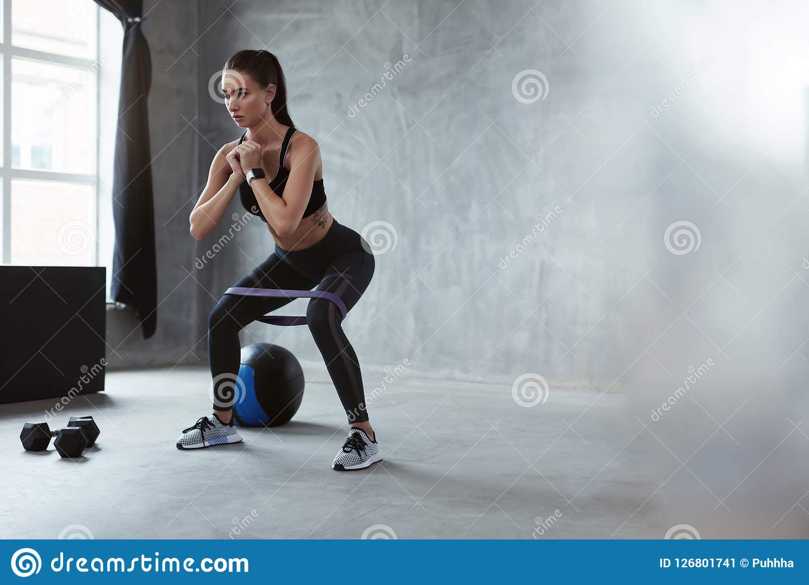 Squats. Sports Woman In Fashion Clothes Squatting With Band