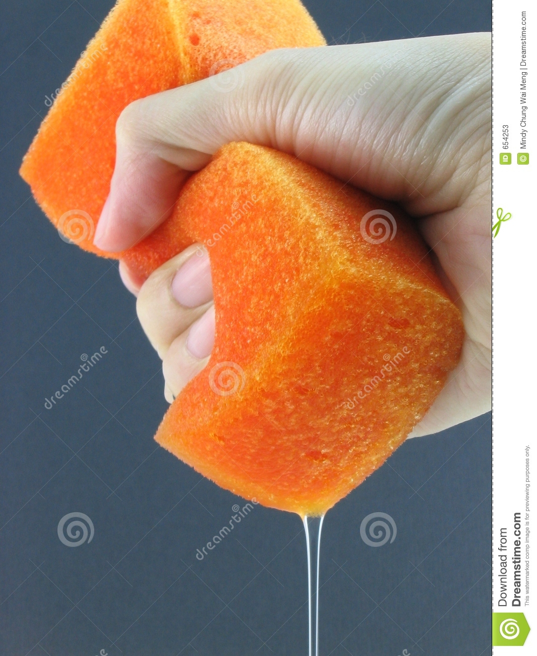 hand squeezing water out from a wet orange sponge.