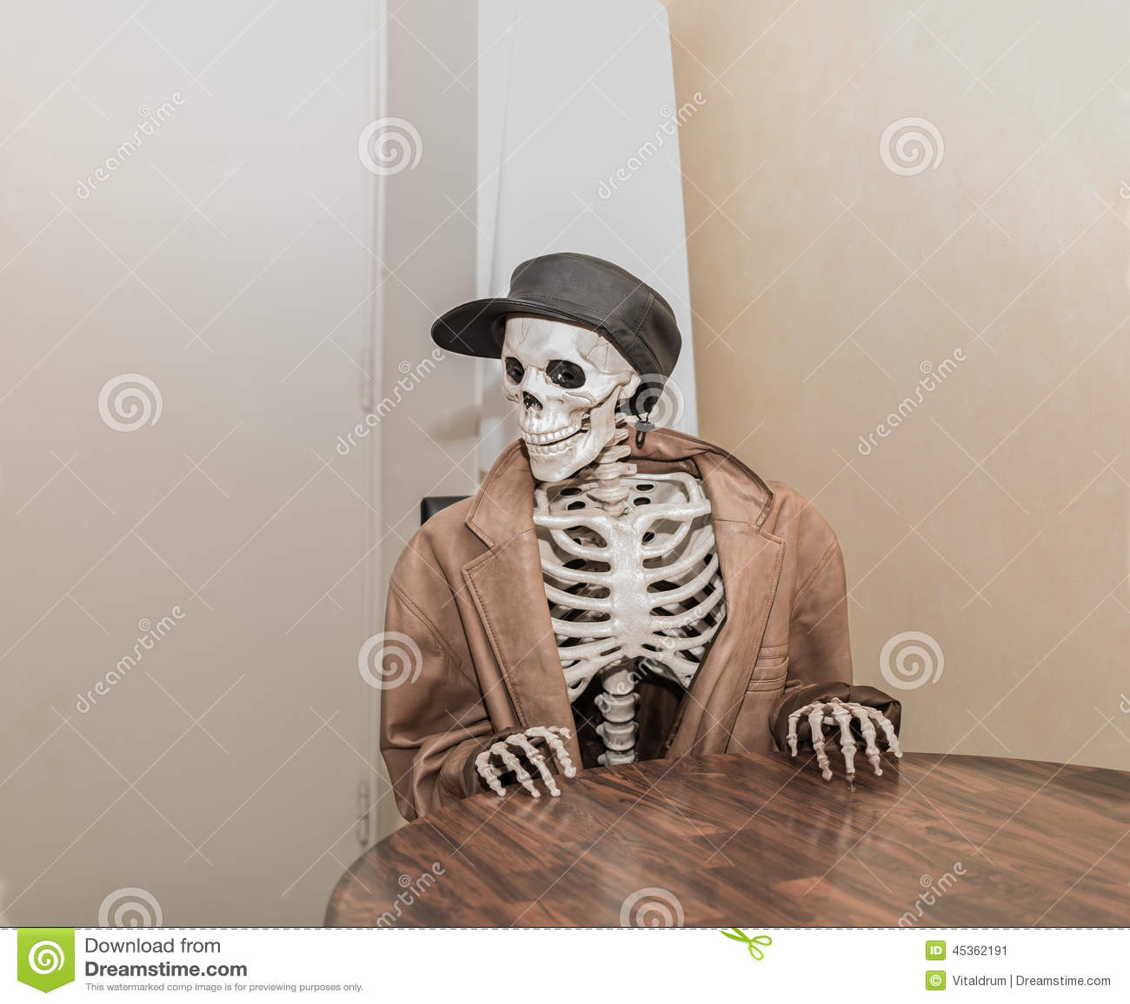Squelette utilisant la veste en cuir brune avec le chapeau en cuir, se reposant derrière la table