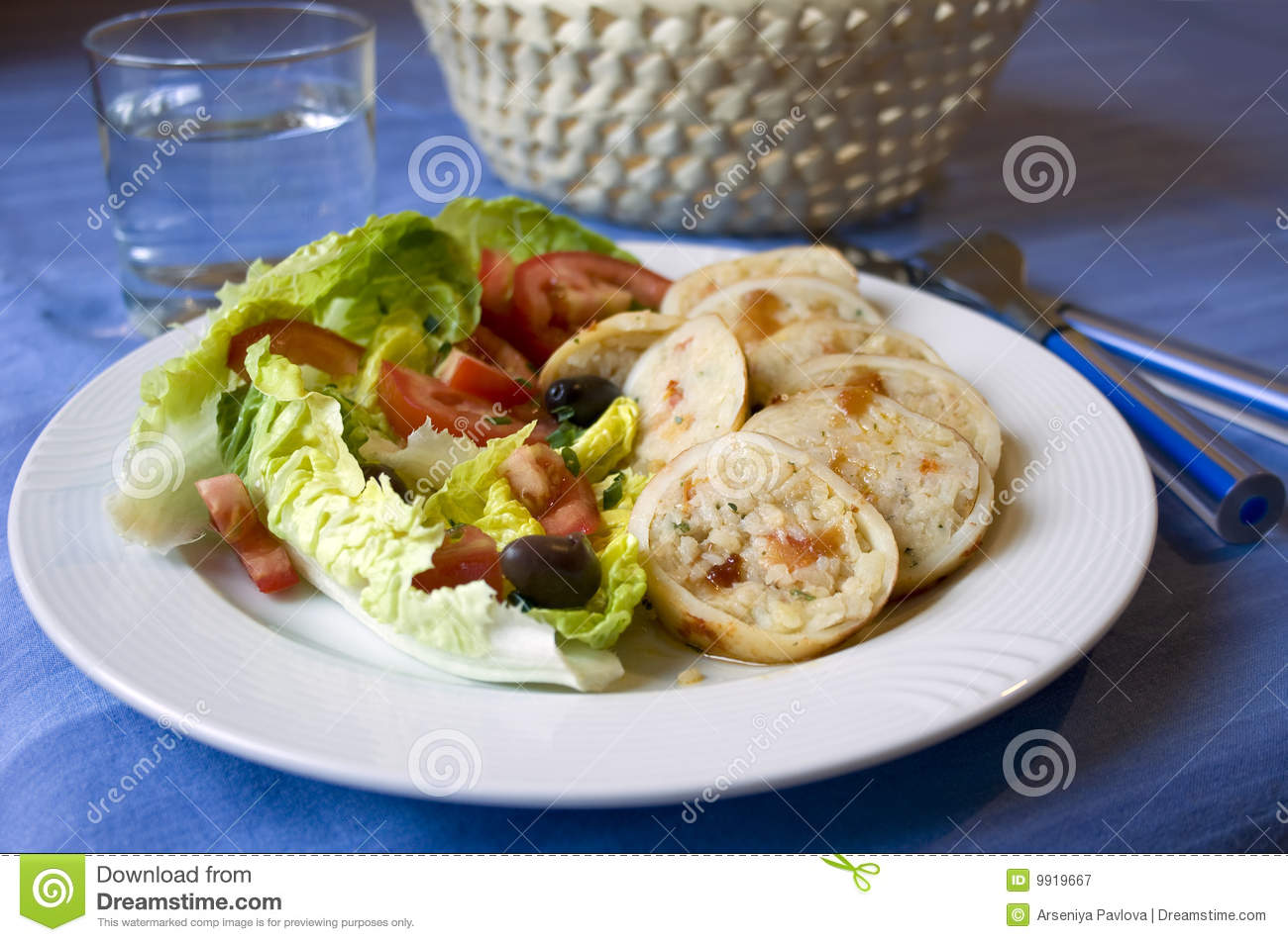 Table with rice stuffed calamari with herbs and greek salad, bread ...