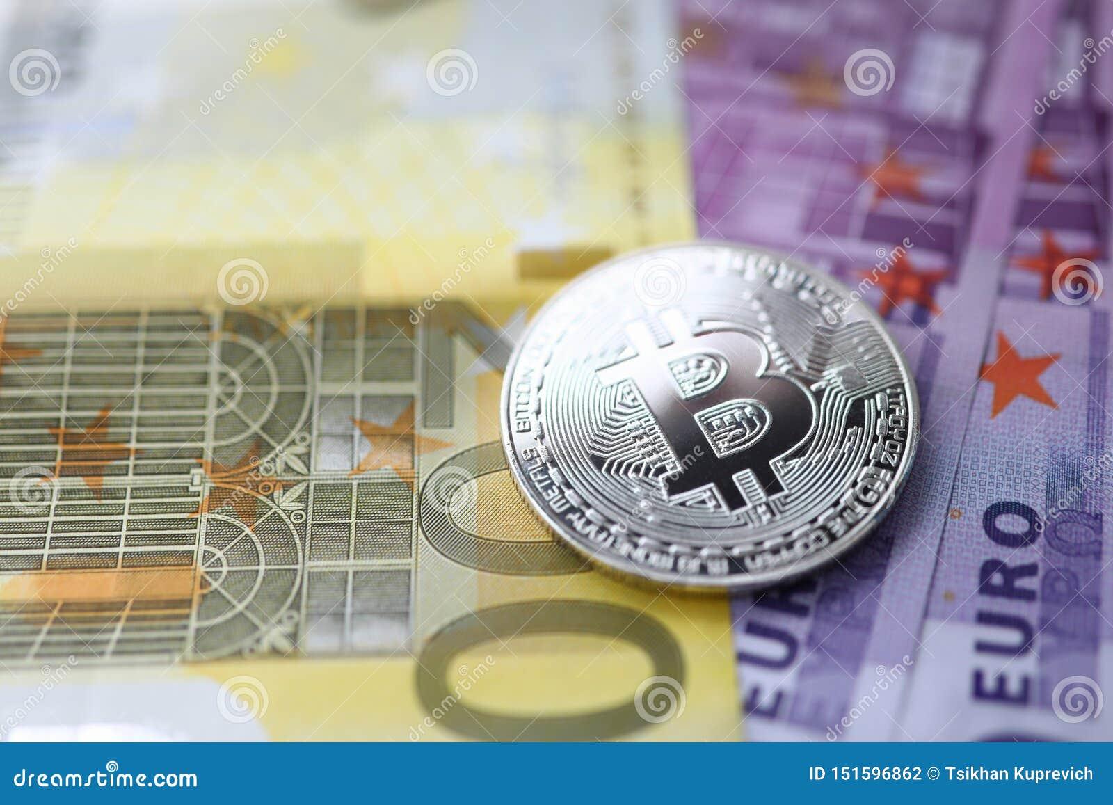 Srebny bitcoin z euro gotówki kłamstwem na stole