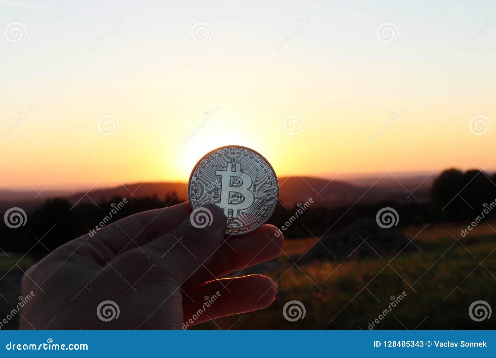 Srebny bitcoin z jasnym niebieskim niebem i zmierzchem Także z piękną łąką