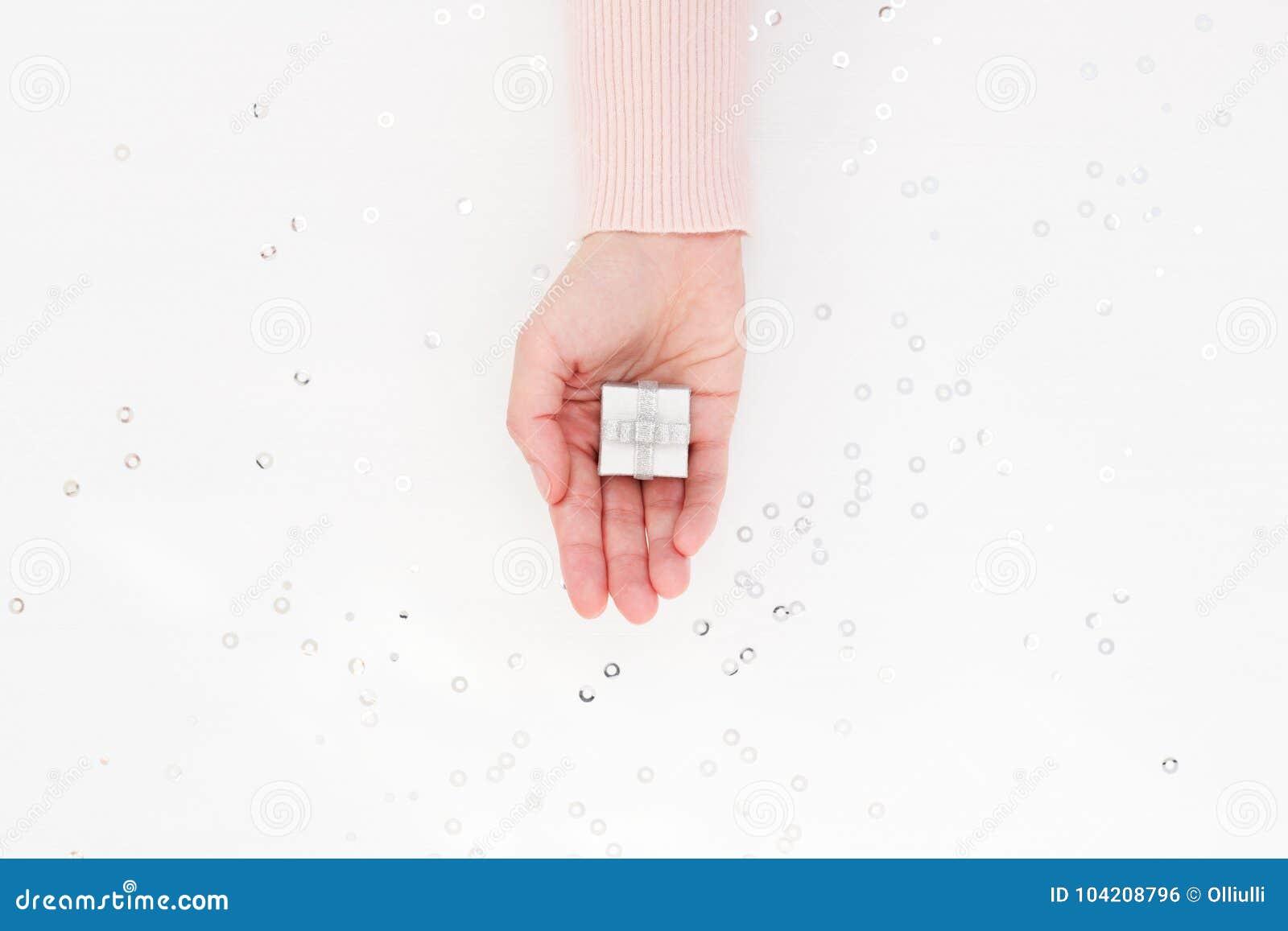 Srebny prezenta pudełko w żeńskiej palmie