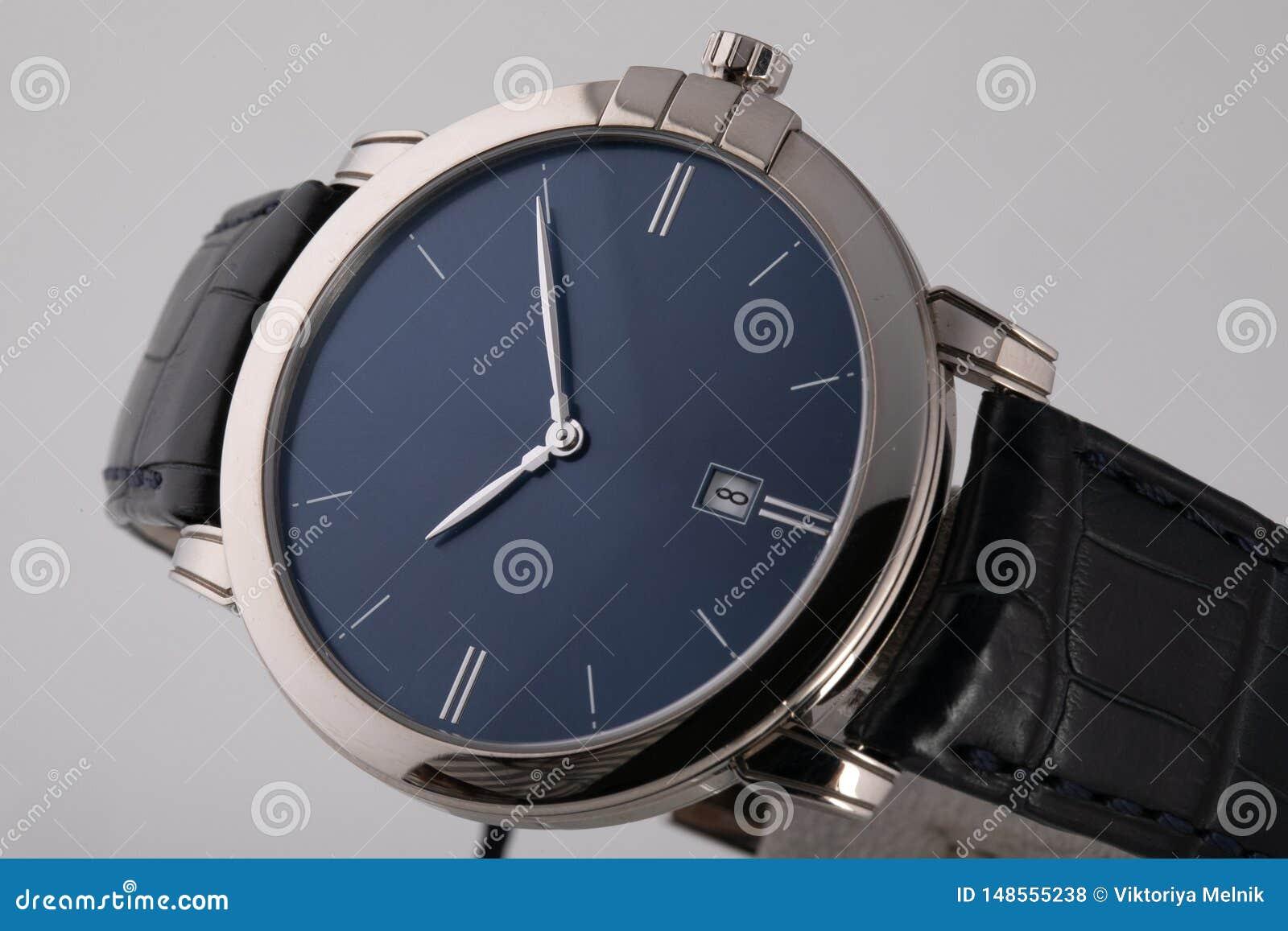 Srebny wristwatch z błękitną tarczą, osrebrza clockwise, chronograf na czarnej rzemiennej patce na białym tle