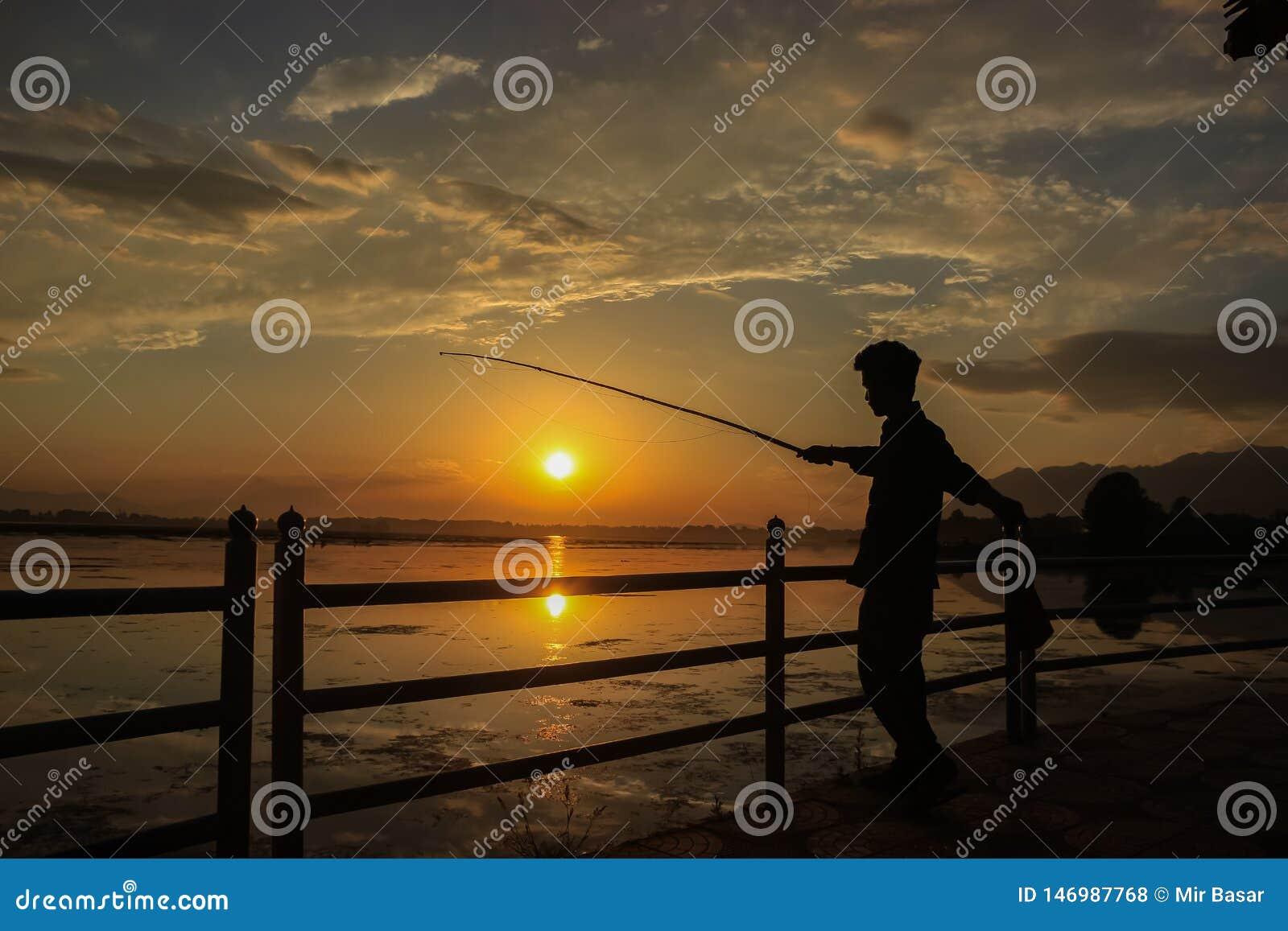 Srinagar, Jammu en Kashmir, India: Gedateerd 18 April, 2019: Een persoon die op de banken van Dal Lake in Kashmir vissen Een pers