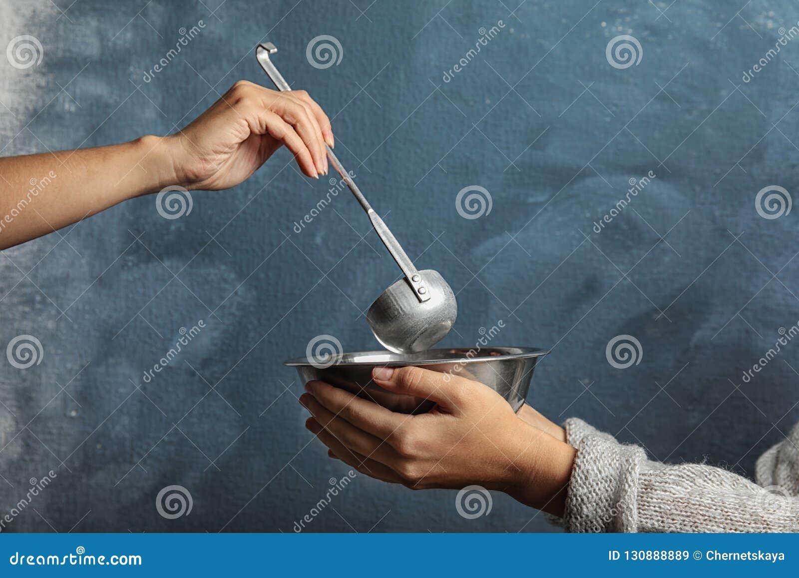 Ställa upp som frivillig sätta mat in i bunken av den fattiga kvinnan på färgbakgrund, closeup