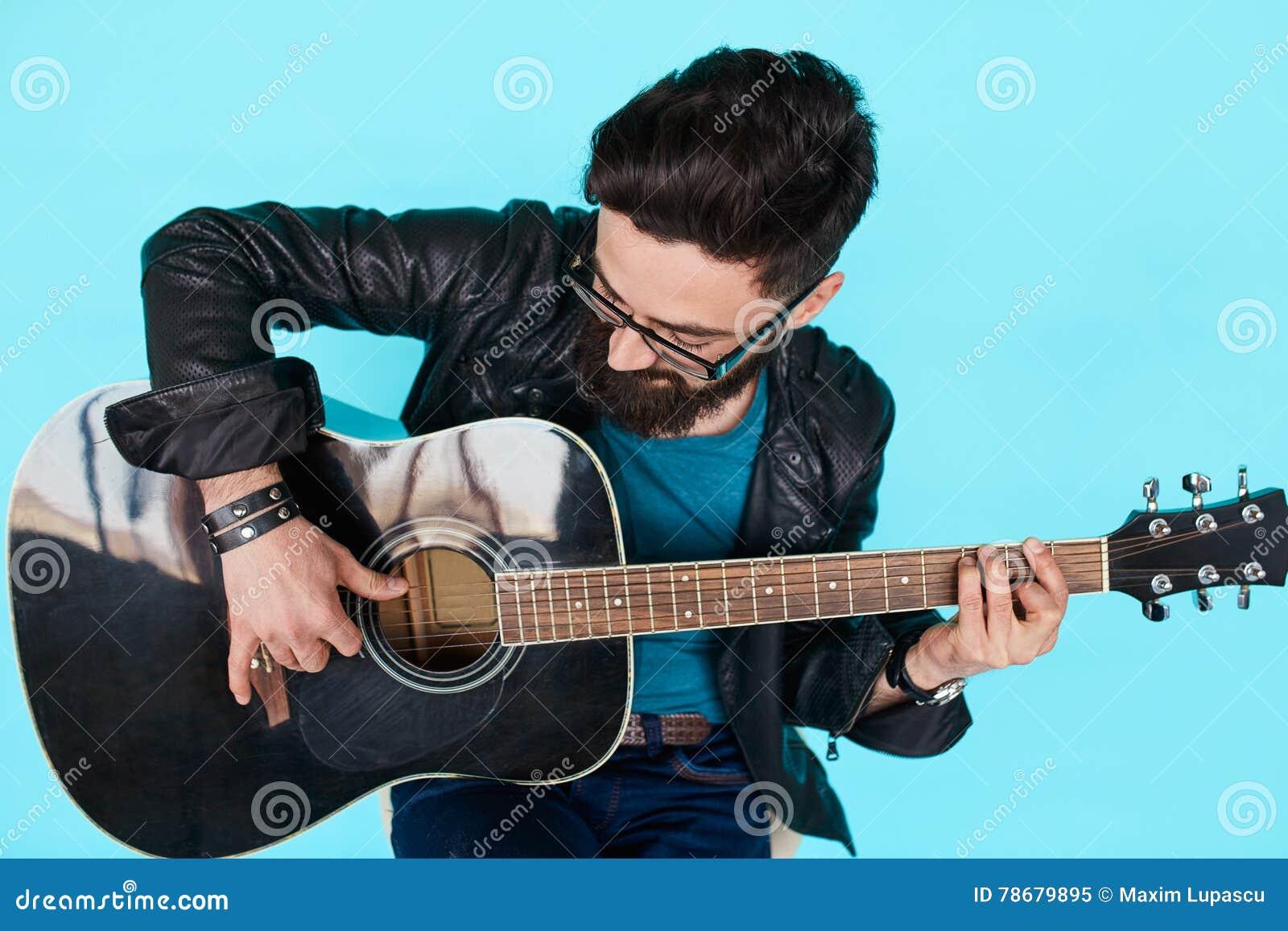 Stäng den skäggiga hipstermannen som spelar på den akustiska gitarren