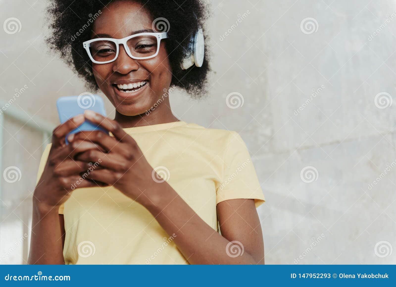 Stäng sig upp av afrikanskt bära för dam som är tillfälligt, och att hålla mobiltelefonen i armar