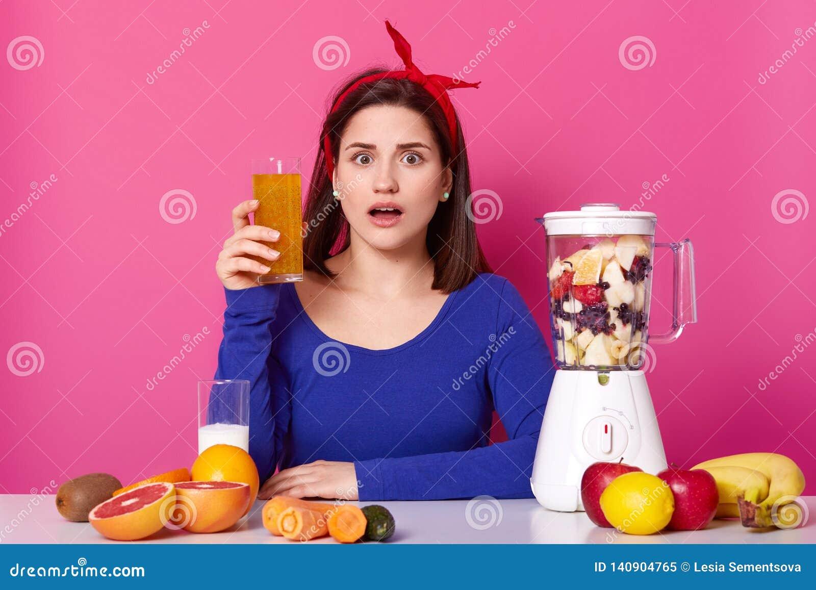 Stäng sig upp av brunettkvinna med exponeringsglas av ny orange fruktsaft i hand Damen gillar sunt äta som hemma gör smoothien fö