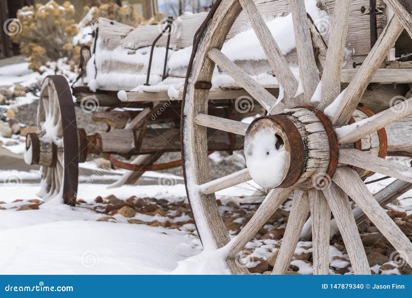 Stäng sig upp av de rostiga hjulen av en riden ut trävagn som beskådas i vinter