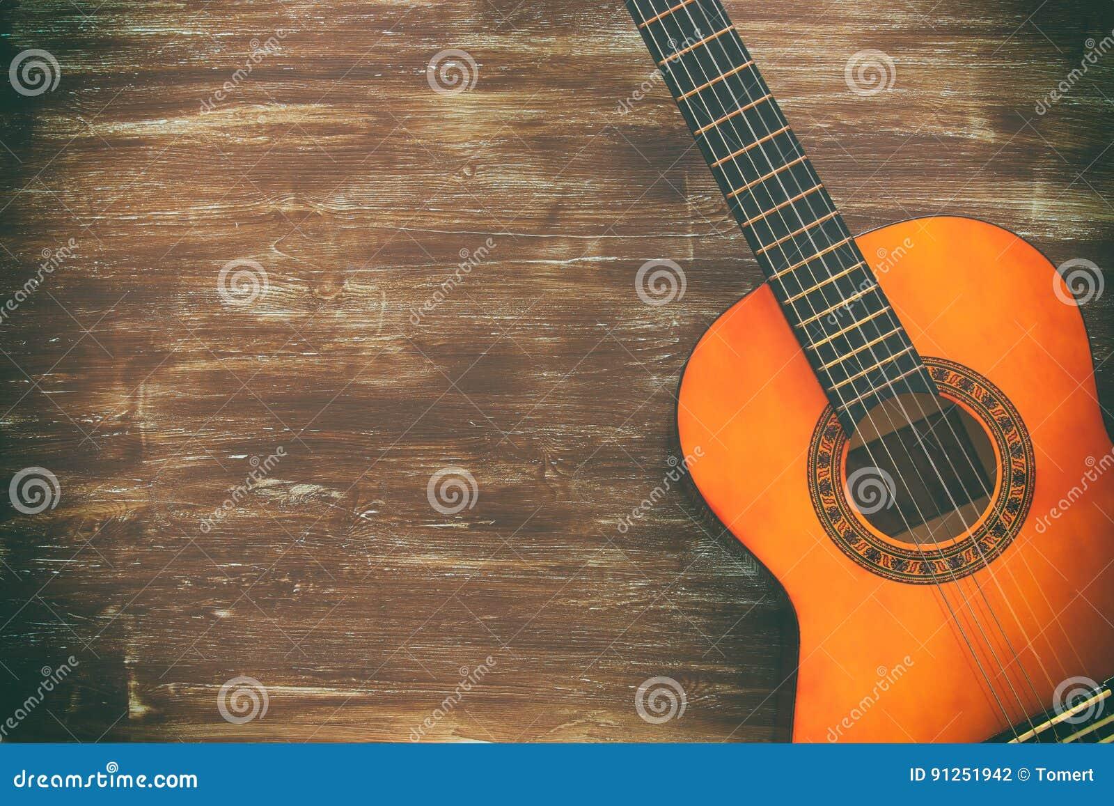 Stäng sig upp av den akustiska gitarren mot en träbakgrund