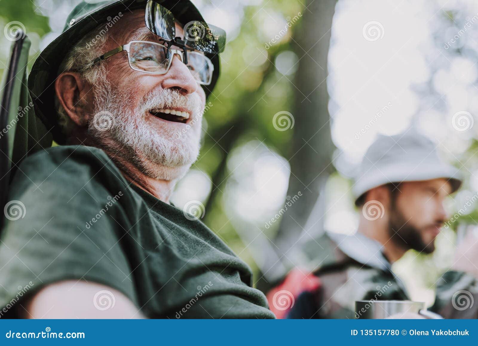 Stäng sig upp av en glad gamal man som utomhus vilar