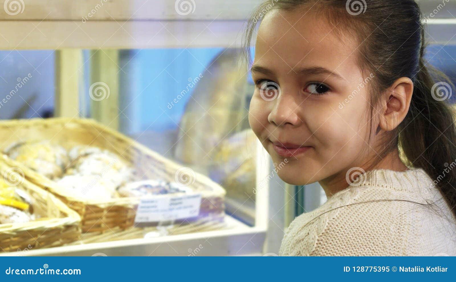 Stäng sig upp av en gullig liten flicka som ler till kameran på bagerit