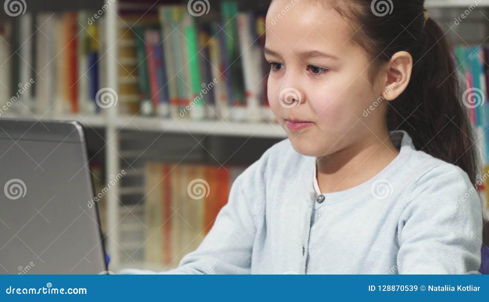 Stäng sig upp av en nätt liten asiatisk flickamaskinskrivning på bärbara datorn