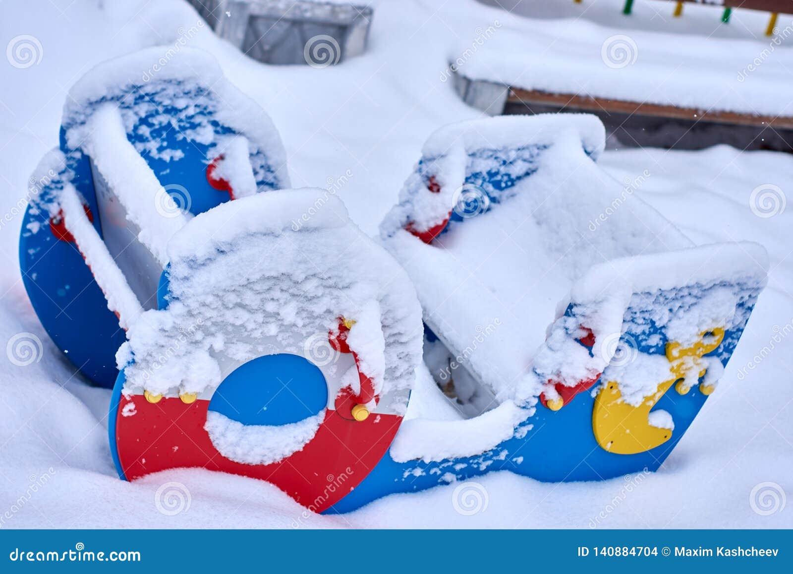 Stäng sig upp av en snö täckt fartyget formad gungbräde för att vackla för att stappla i en barnlek parkerar under den kalla vint