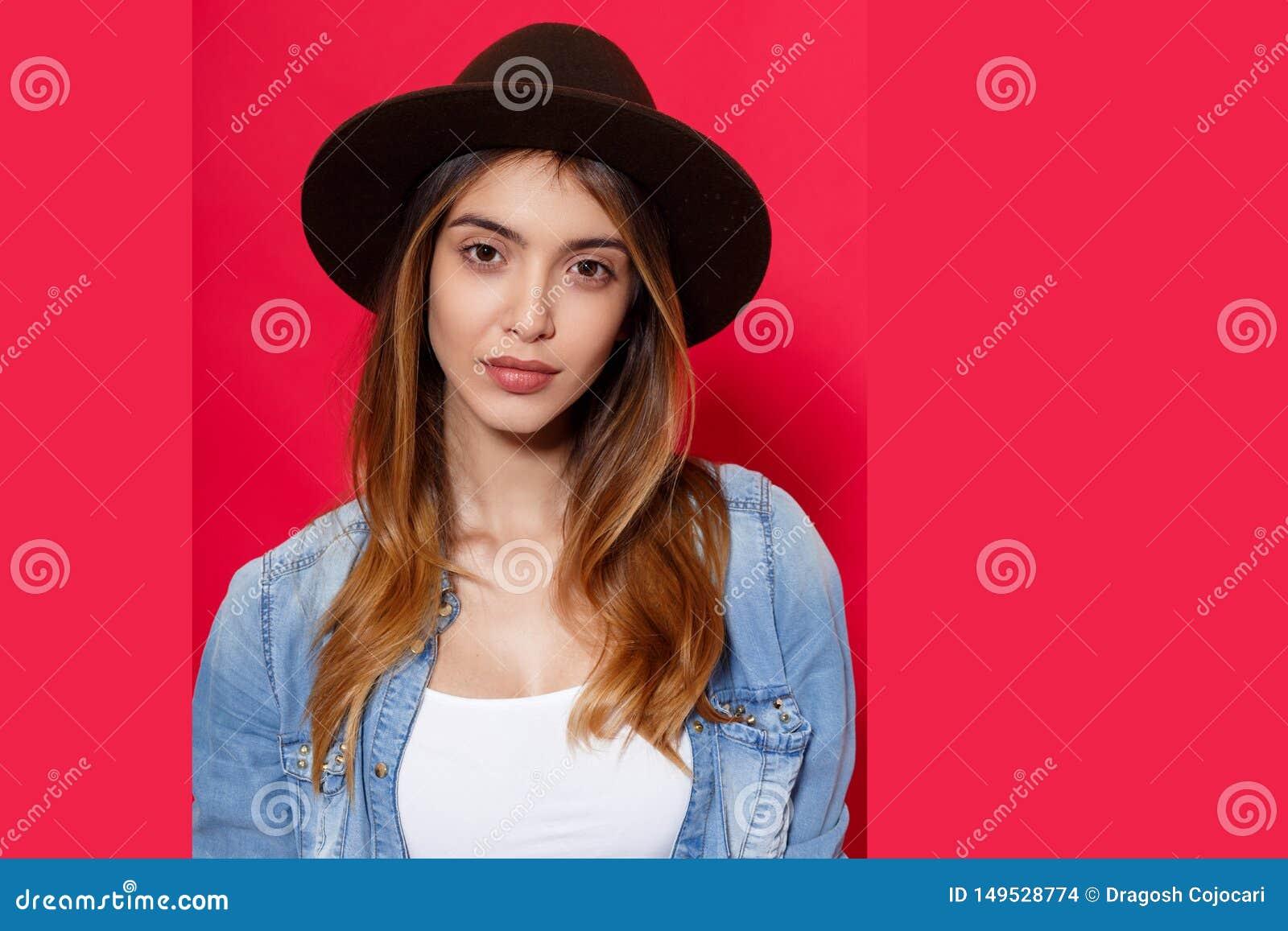 St?ng sig upp av en varm brunettflicka i hatt- och grov bomullstvillskjorta och att se med inst?llning p? kamera, p? r?d bakgrund