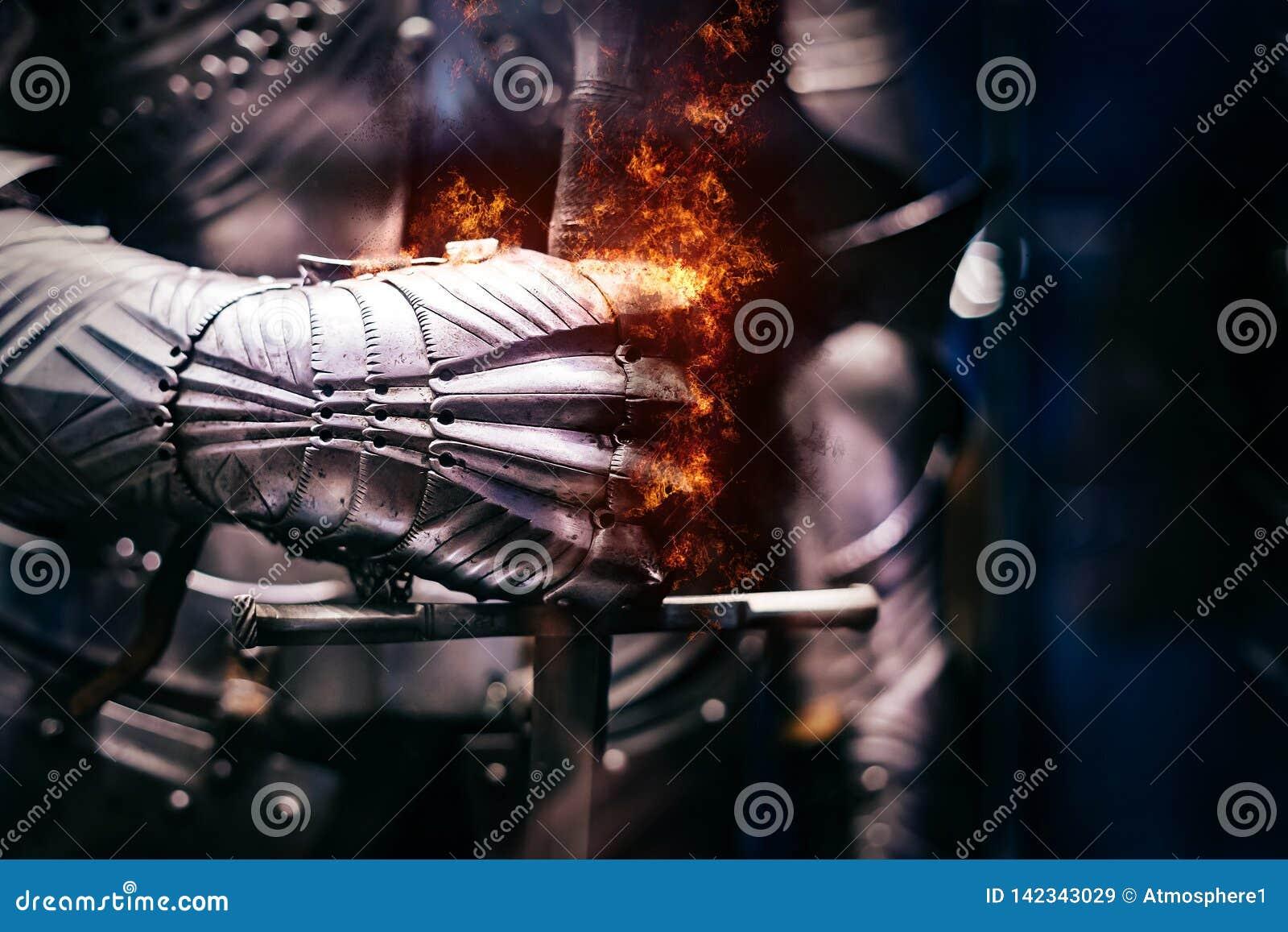Stäng sig upp av ett medeltida stålpansar med järnhandskehanden som brister med flammor av brand