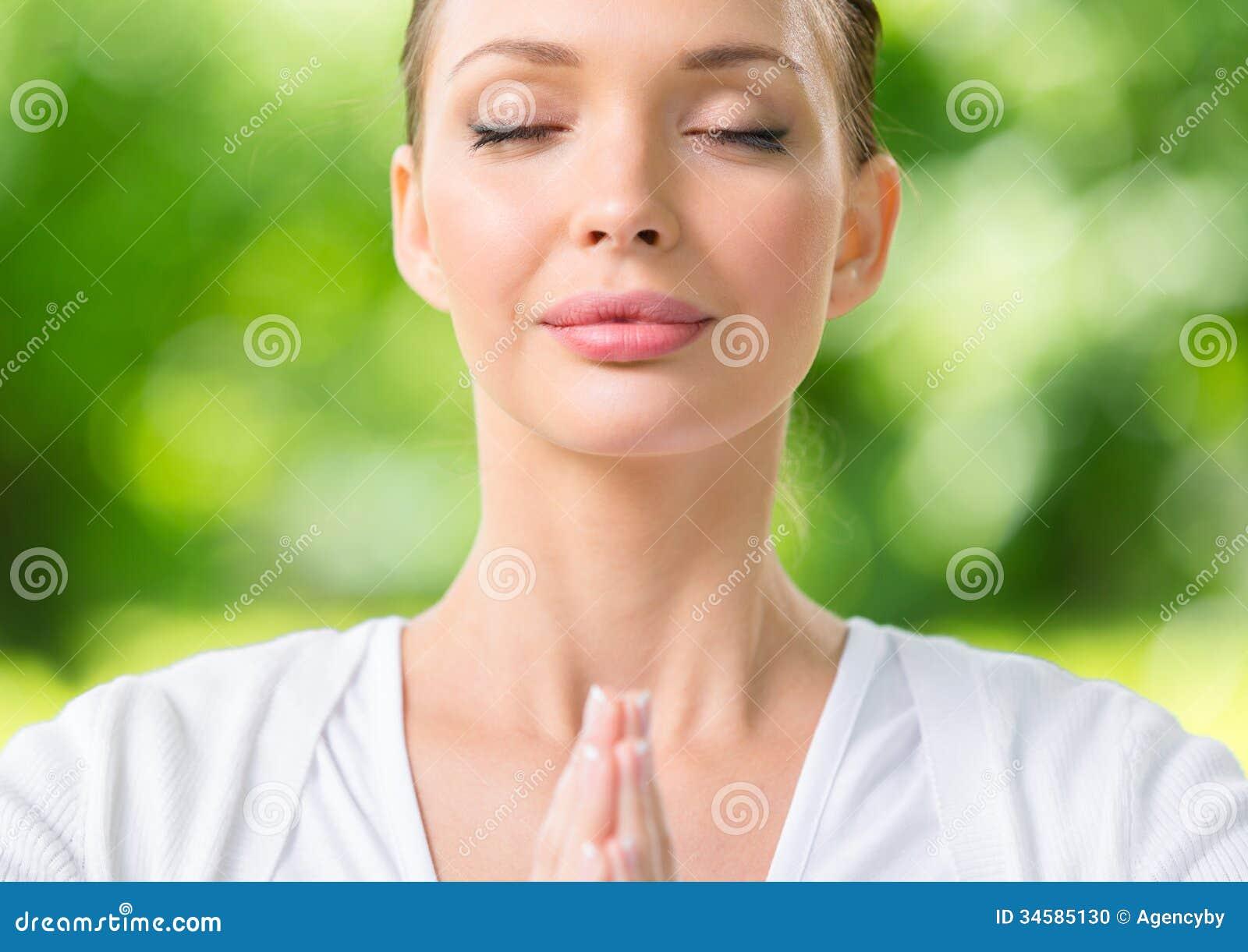Stäng sig upp av kvinna med ögon stängt göra en gest för bön