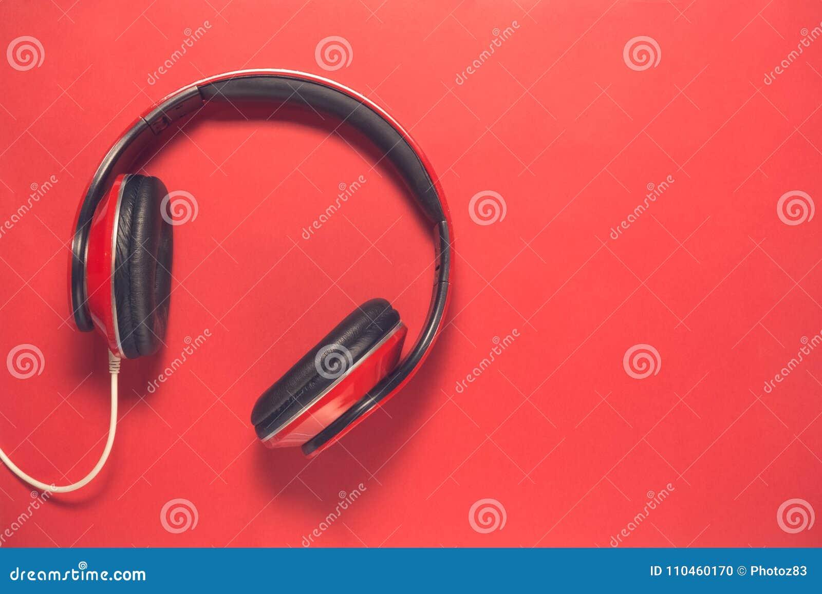 Stäng sig upp av läst hörlurar på röd bakgrund Minsta begrepp för musik
