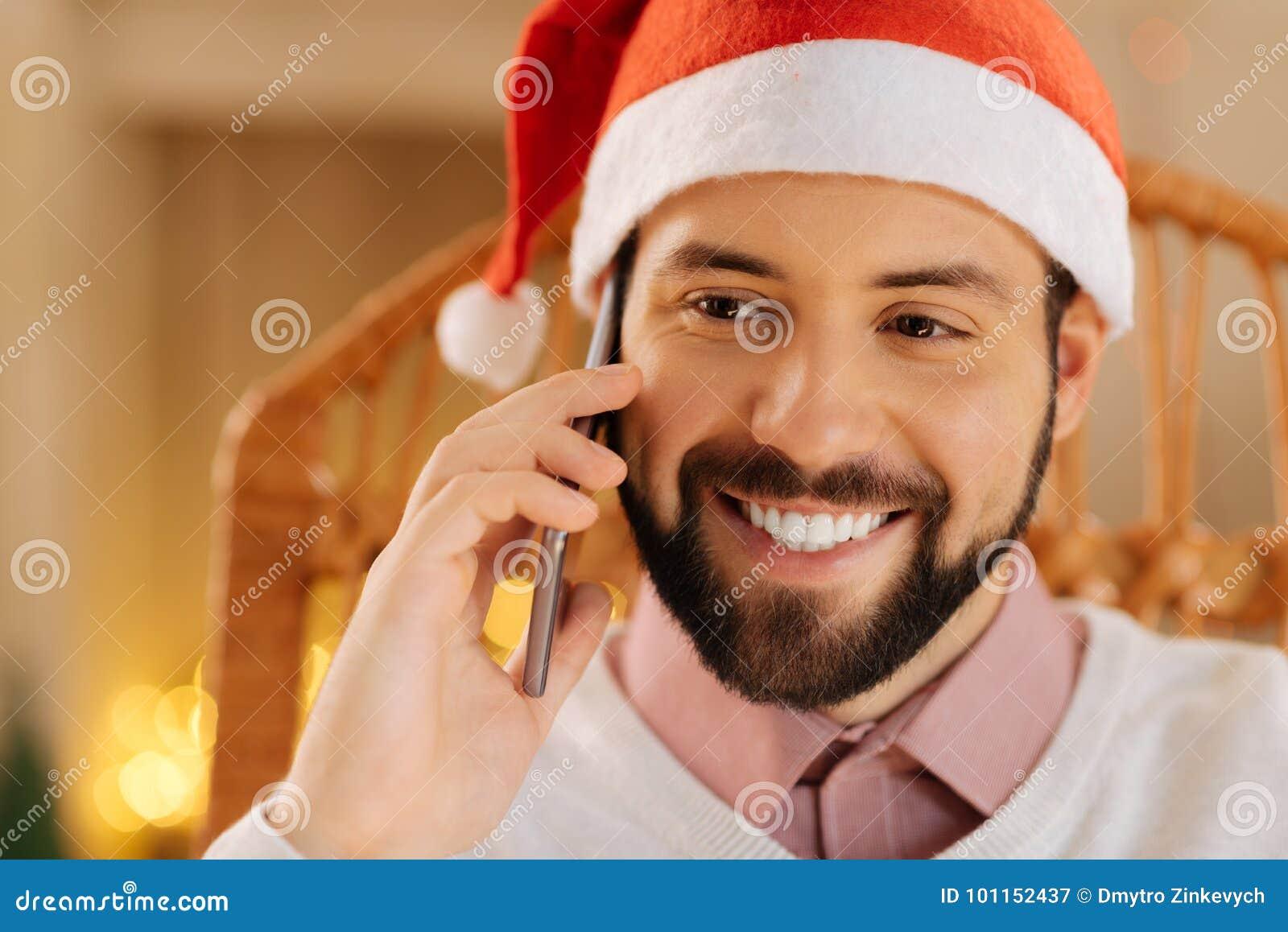 Stäng sig upp av lycklig man i appeller för jultomtenhattdanande