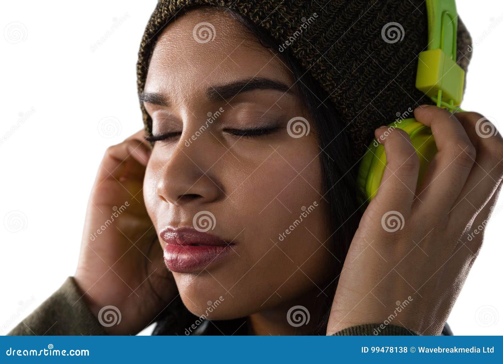 Stäng sig upp av lyssnande musik för kvinna på hörlurar